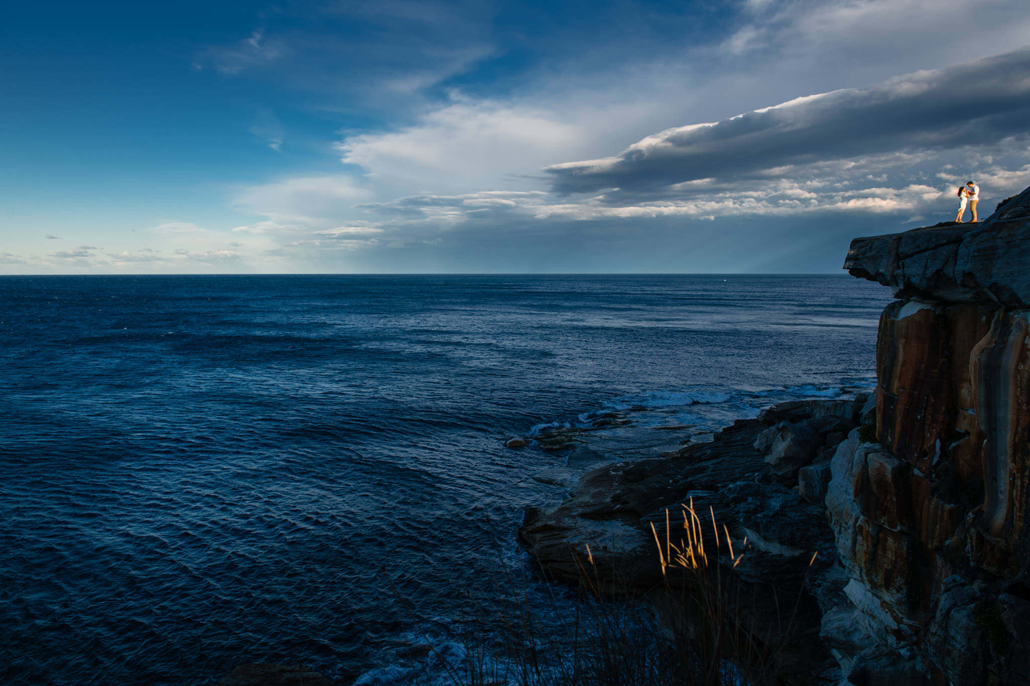 Panoramic view of the ocean from South head with couple dancing on a cliff top