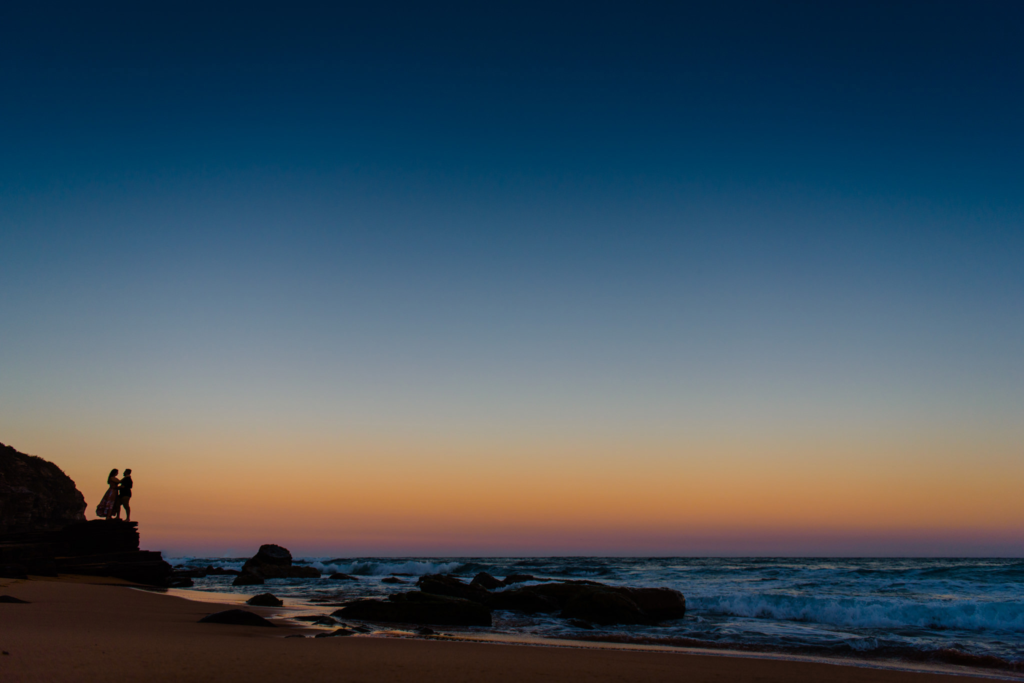 Silhouette of couple against bright sunset colours at Turimetta Beach