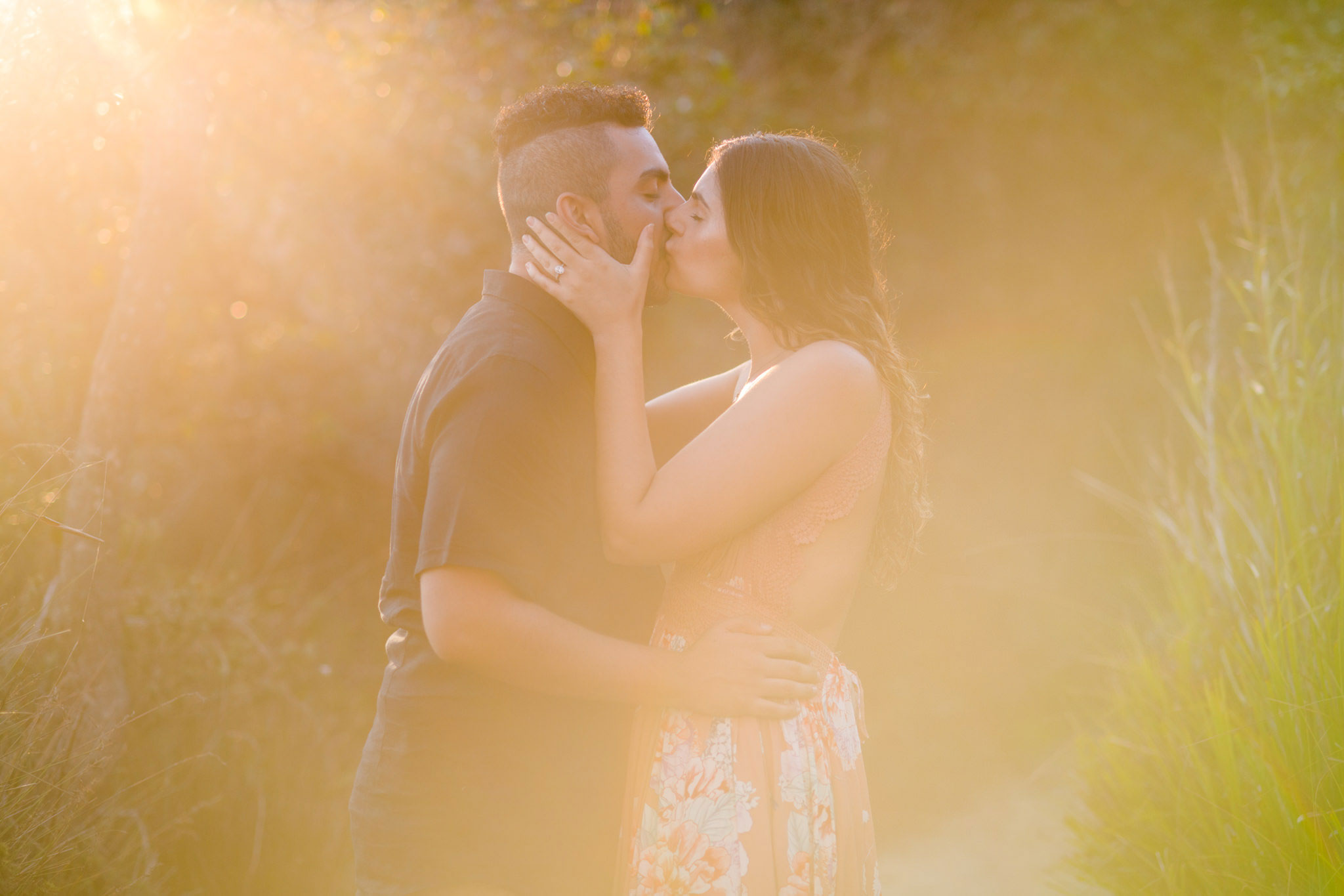 Backlit image of engaged couple kissing at Turimetta beach