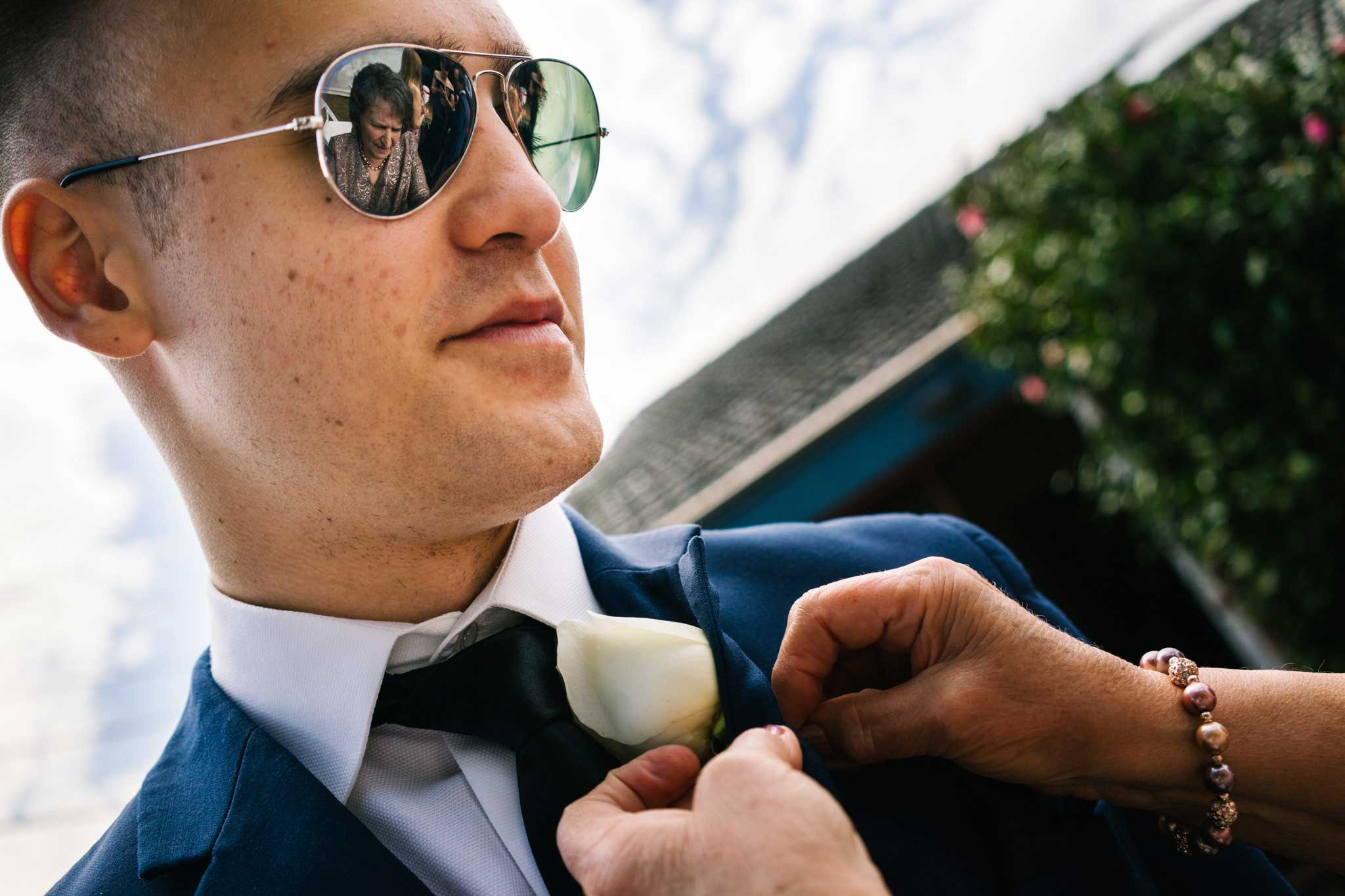 Reflection of grandmother in groomsman's sunglasses as she pins on buttonhole