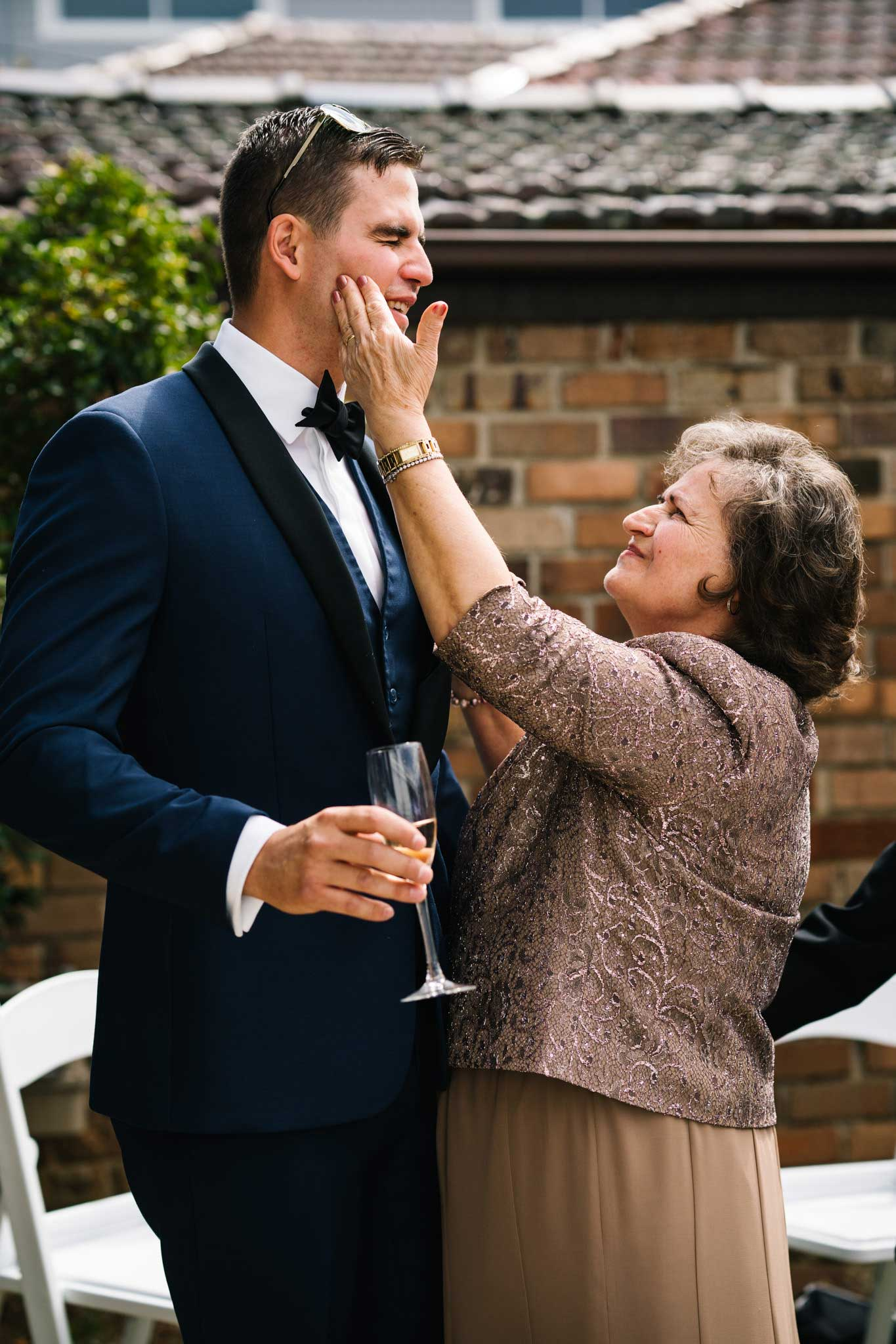 Grandmother playfully slaps groom on the cheek