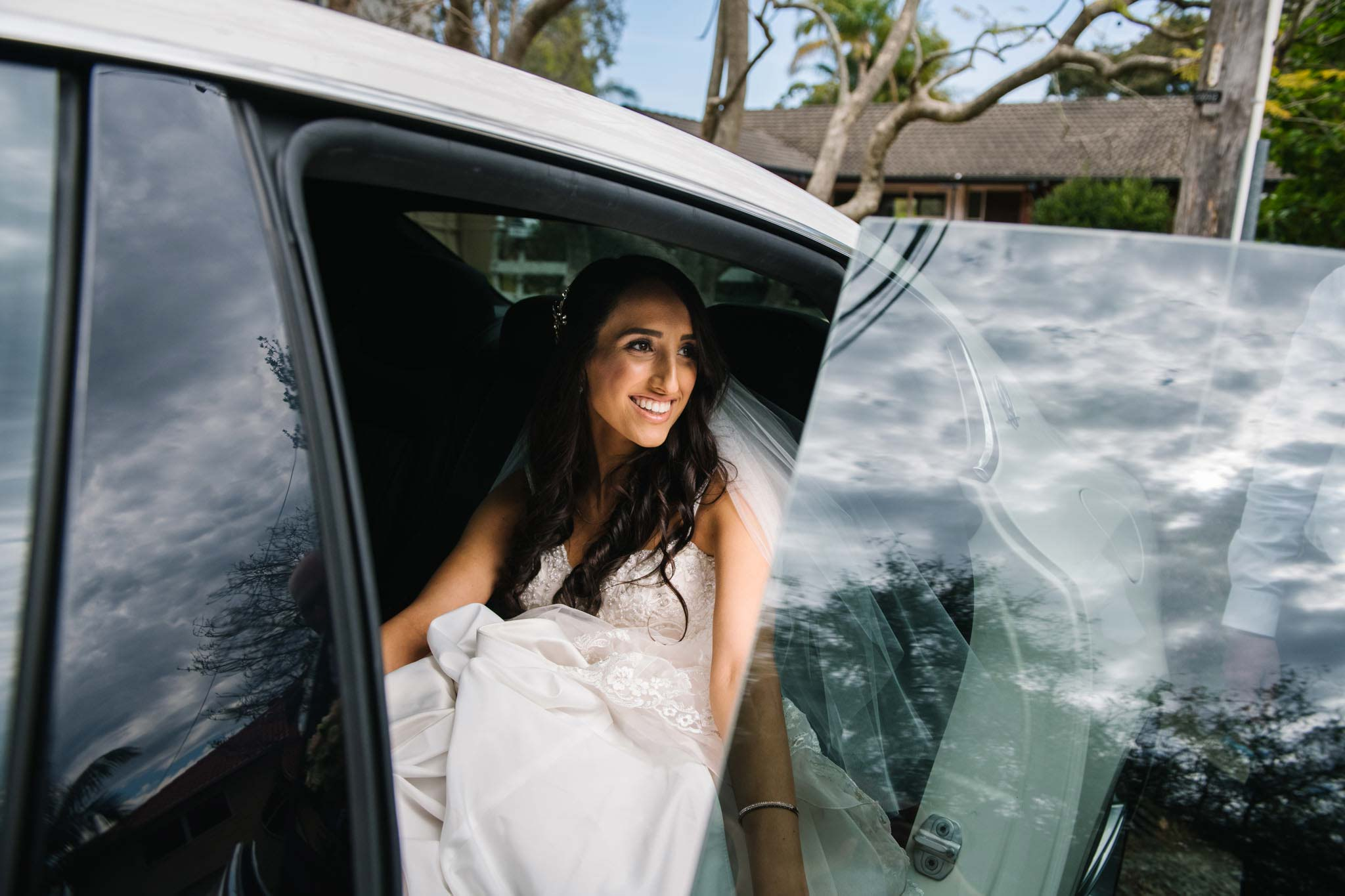 Bride smiling as she climbs into wedding car
