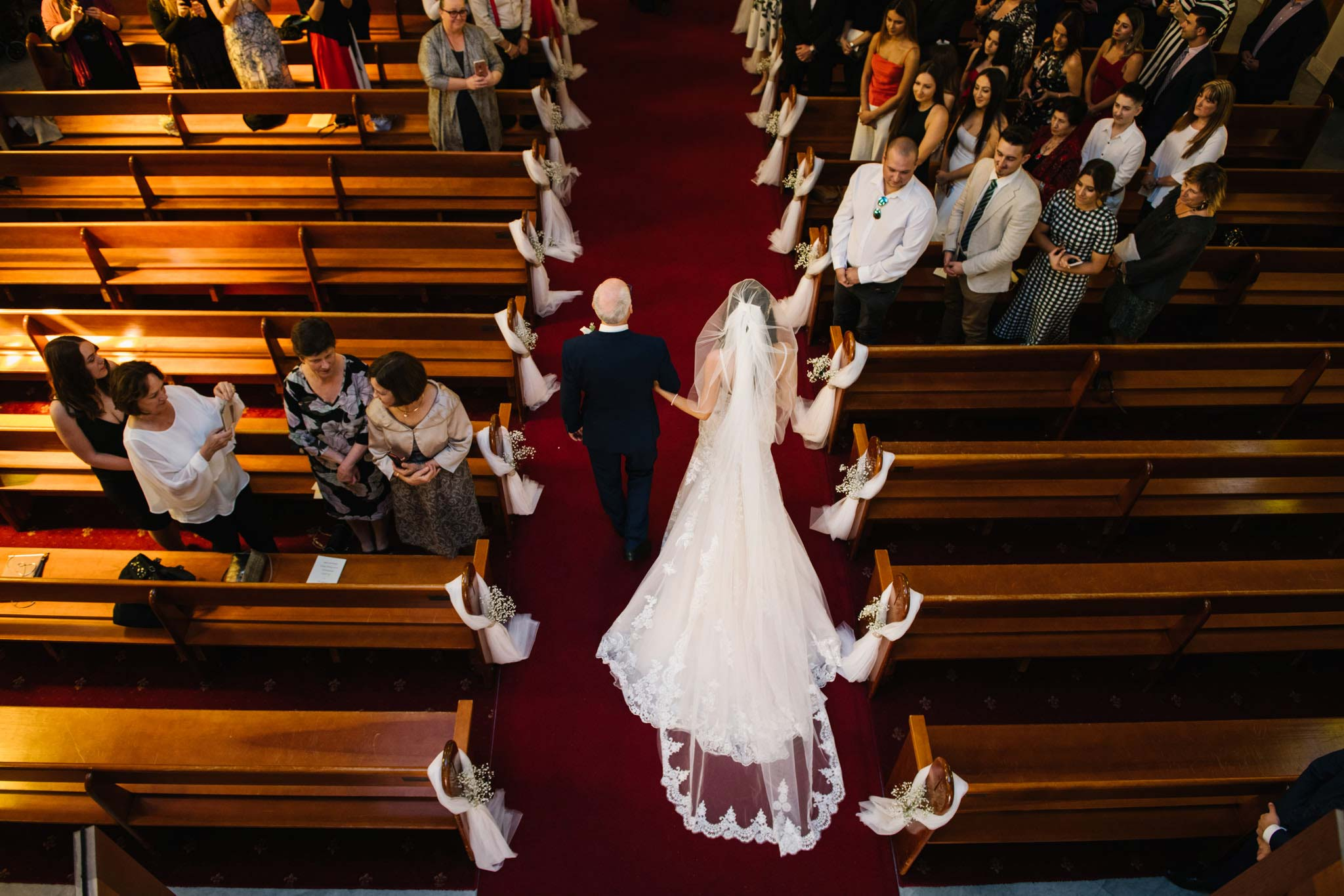 Birds eye view of bride and father entering the church