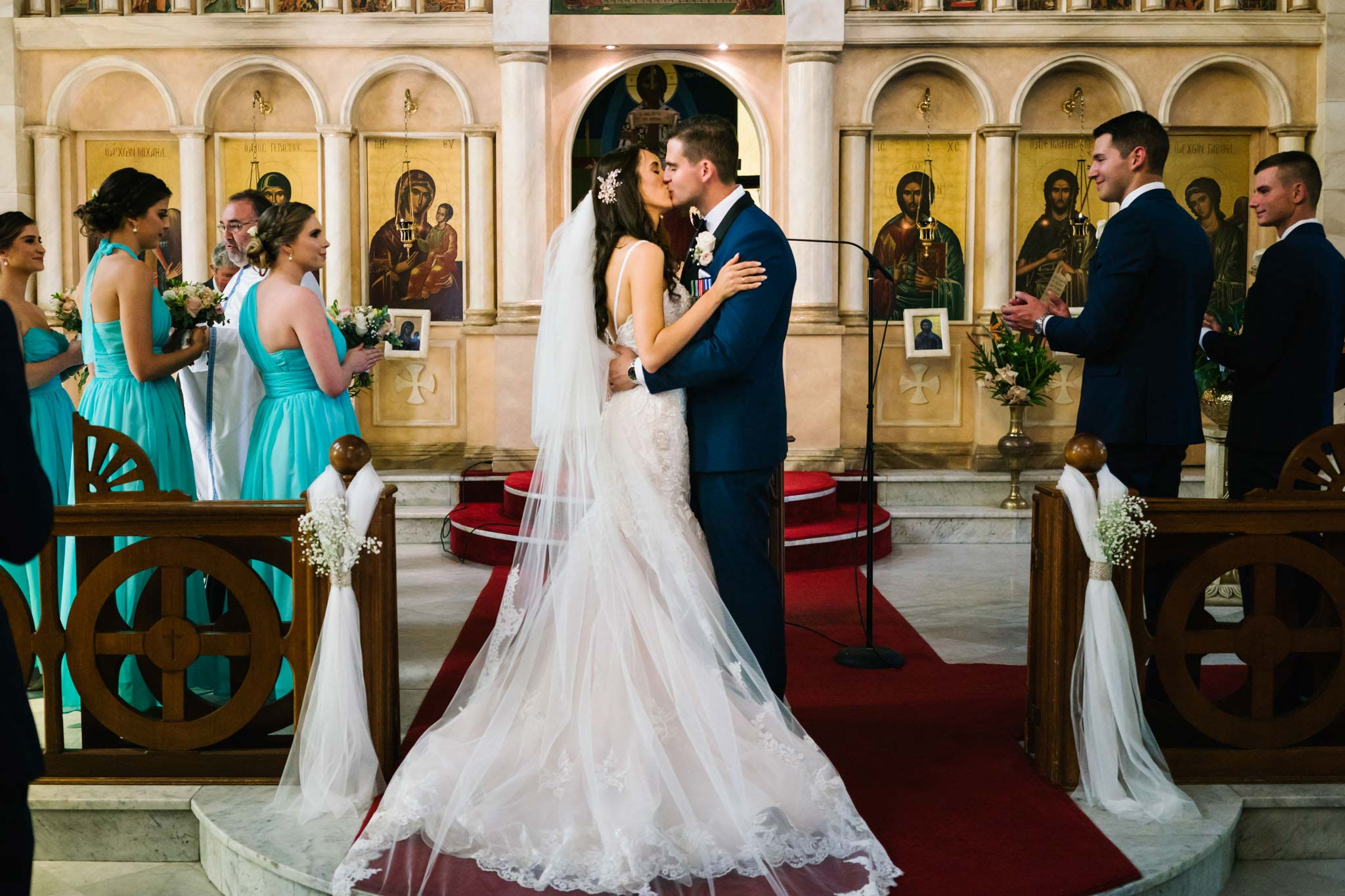 Bride and groom's first kiss during Greek orthodox wedding ceremony