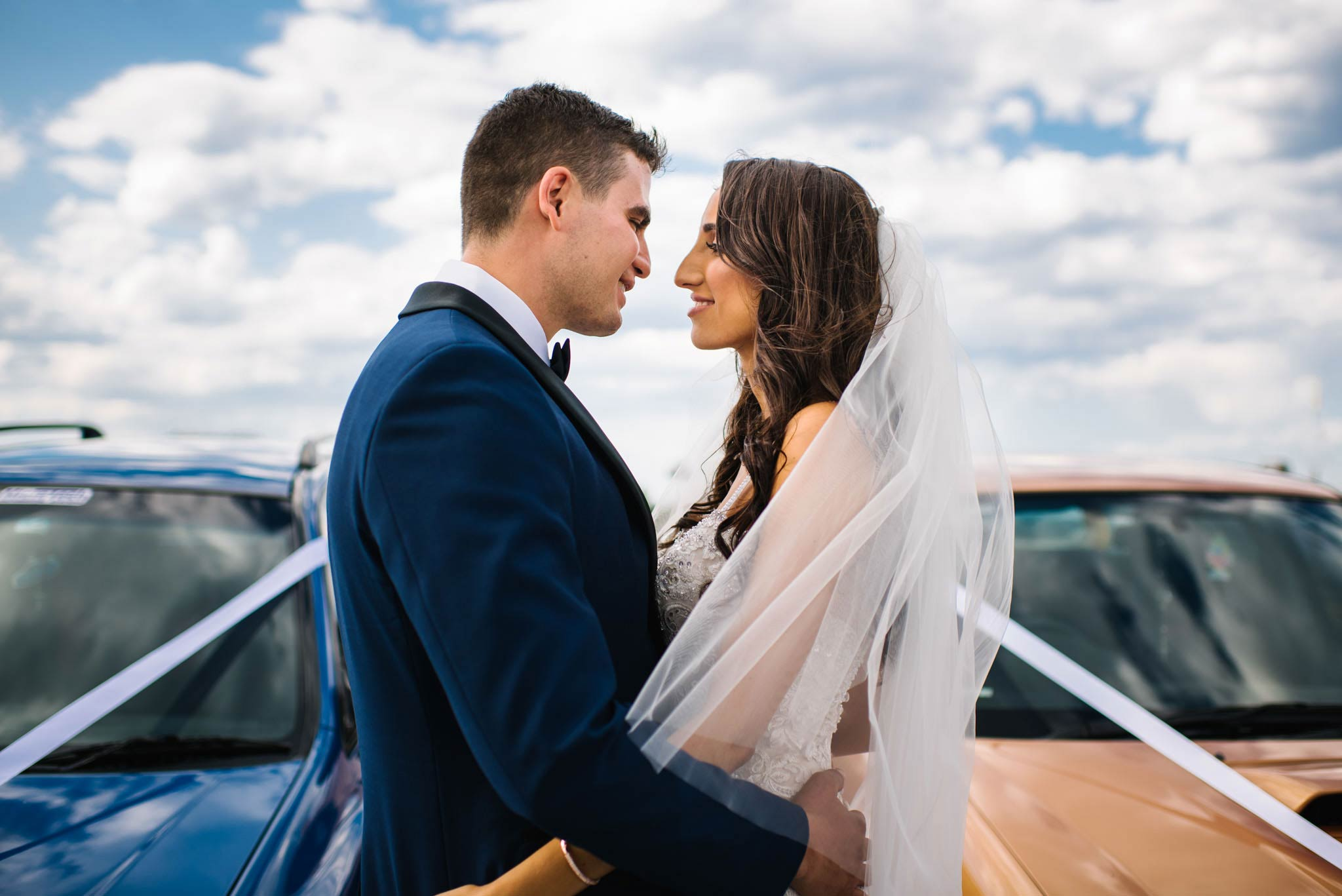 Newlyweds embracing in front of muscle wedding cars