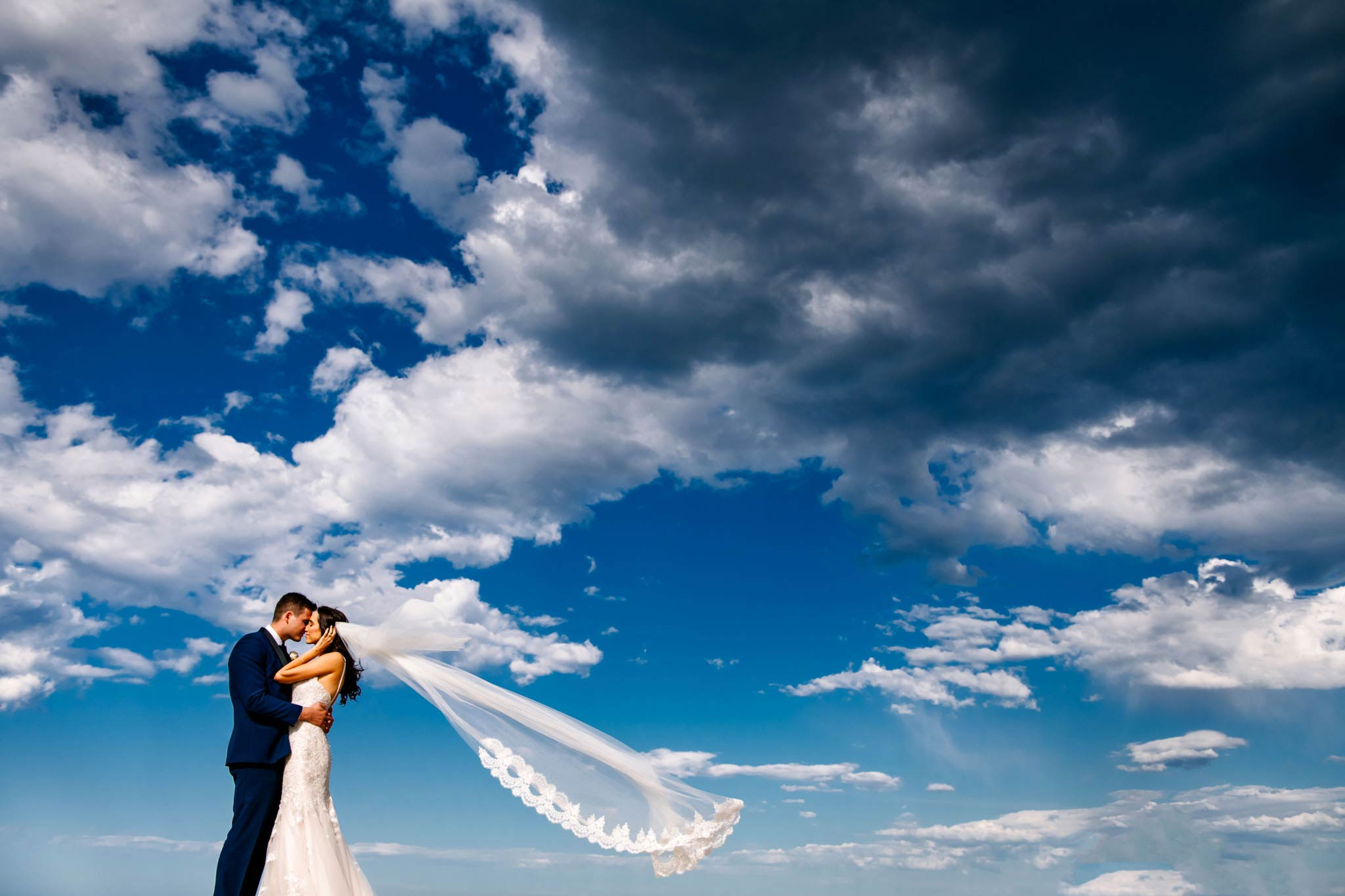 Newlyweds embrace with view of sky behind them as the bride's veil floats in the breeze