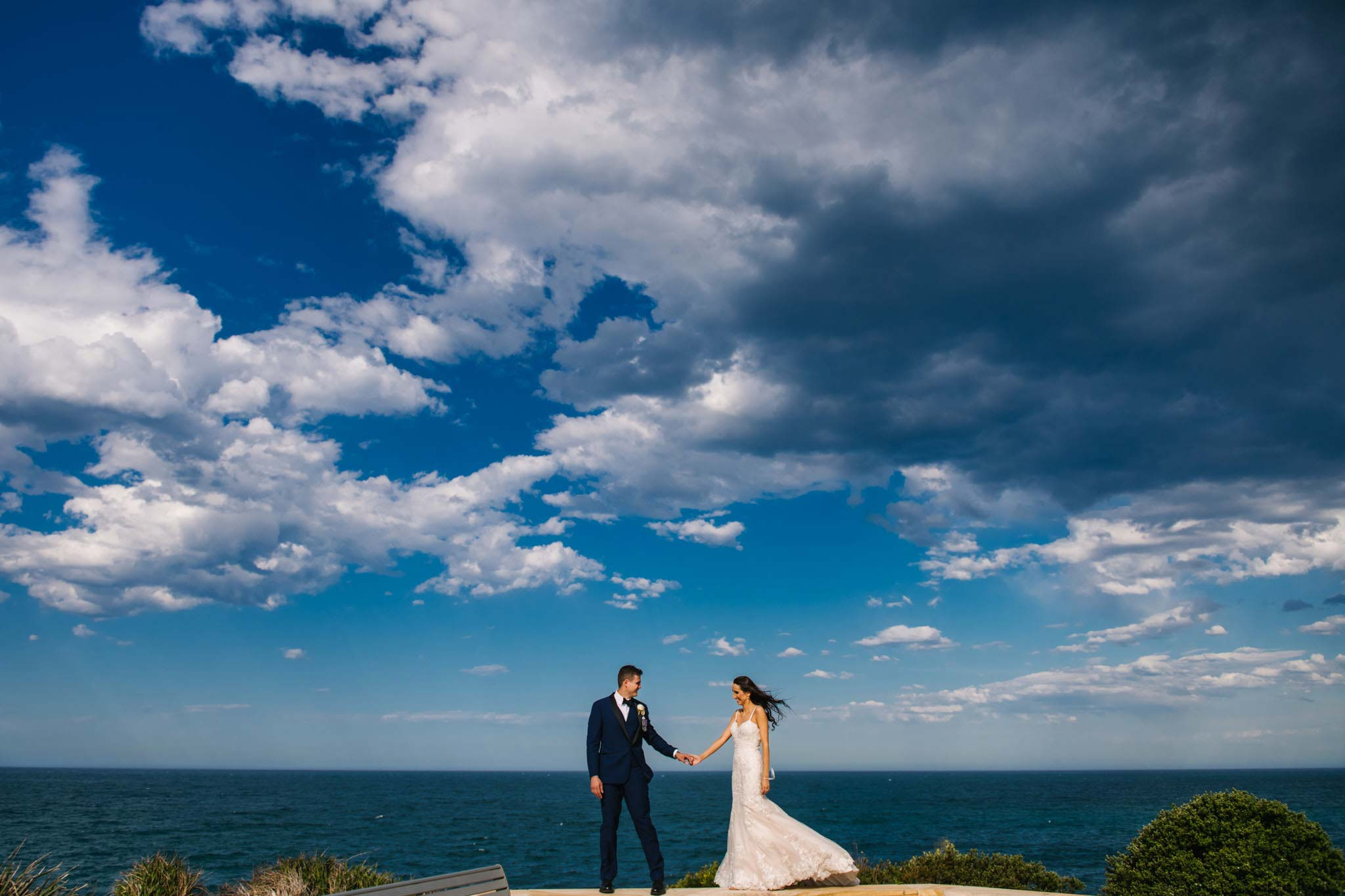 Beautiful view of the ocean at Freshwater headland with newlyweds walking along stone wall