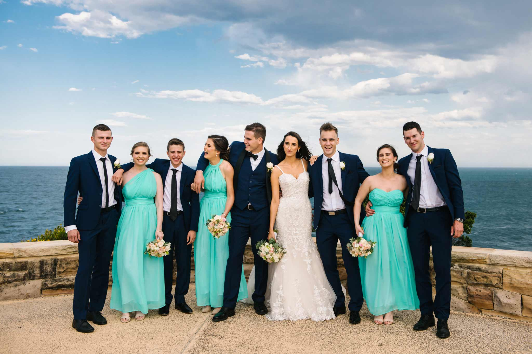 Bridal party laughing at Freshwater lookout in Sydney's Northern Beaches