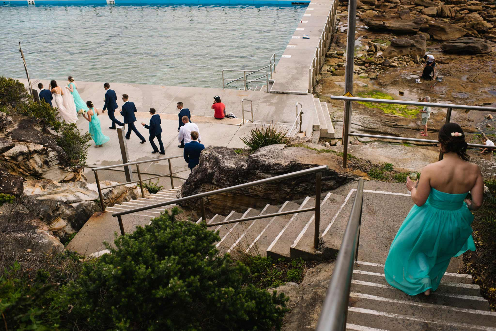Bridal party walking down the stairs towards the tidal pool at Freshwater beach