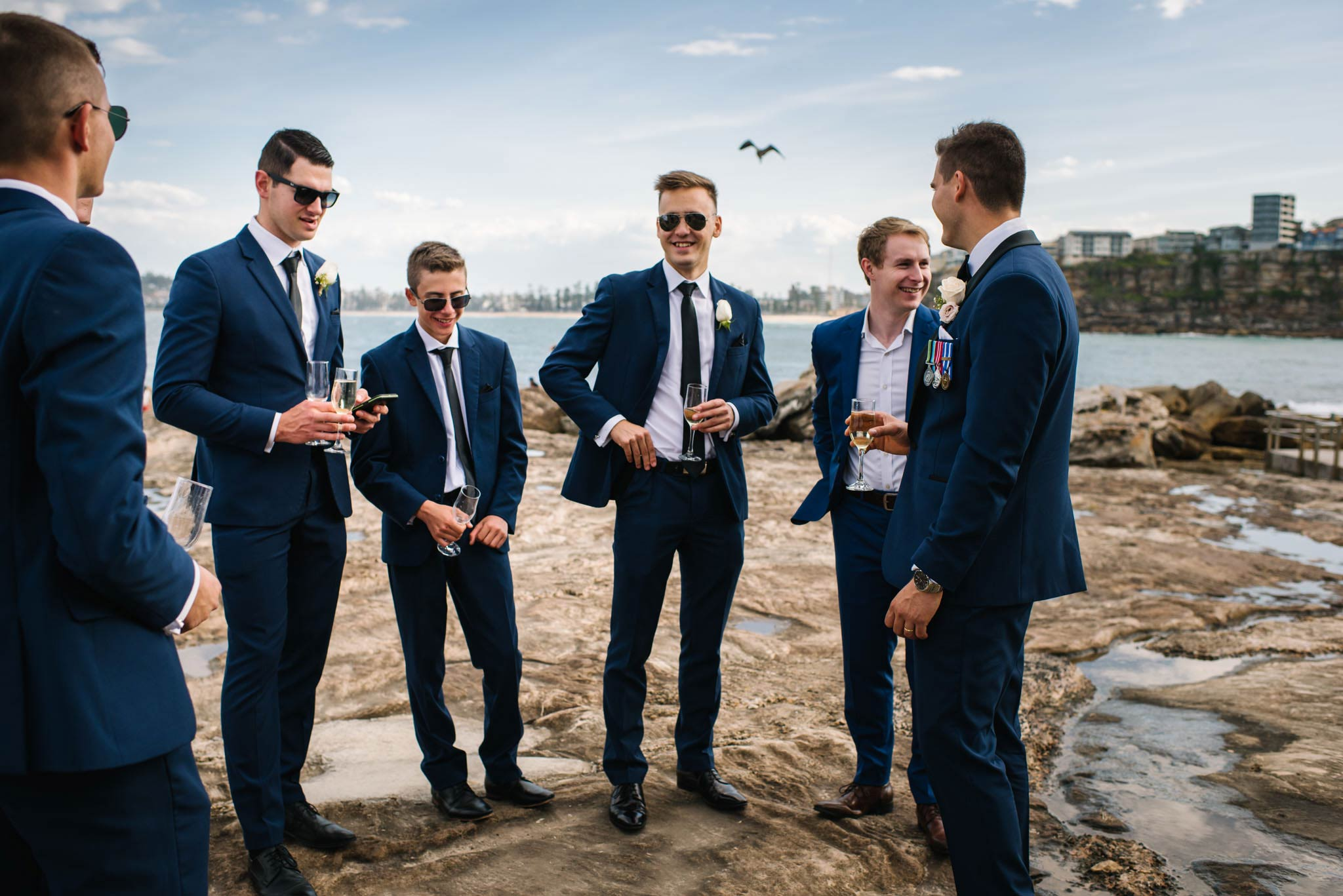 Groomsmen casually chat with Freshwater beach in the backdrop