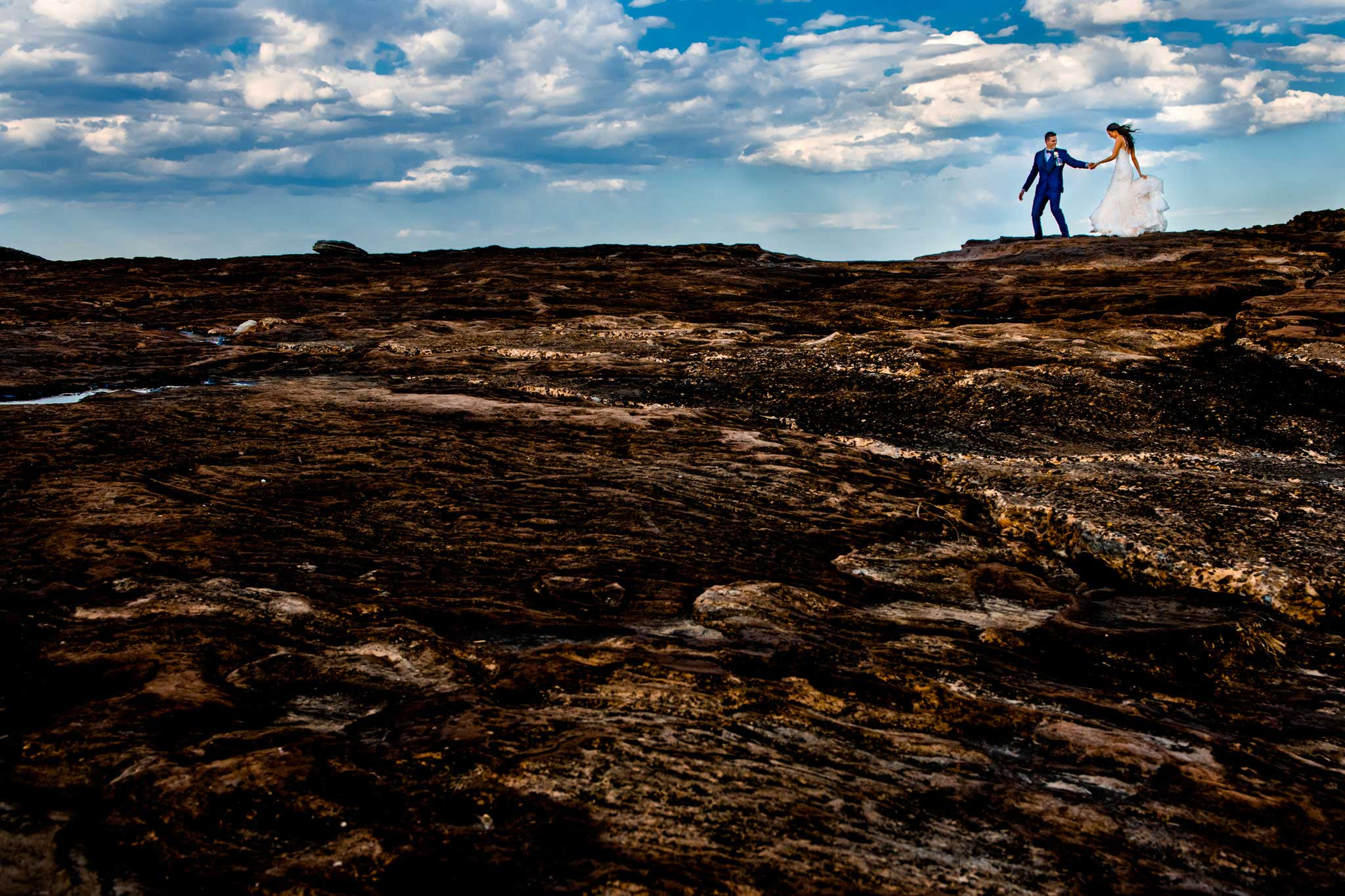 Newlyweds walking along moon-like rocks at Freshwater beach