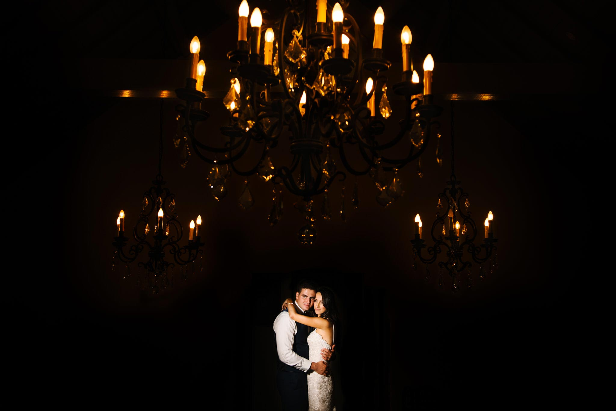 Bride and groom embrace under chandeliers at Manly Golf Club wedding reception
