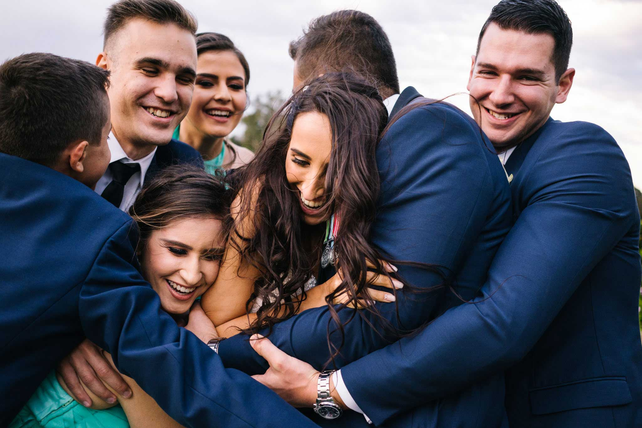 Bridal party embracing newlywed couple at Manly Golf Course