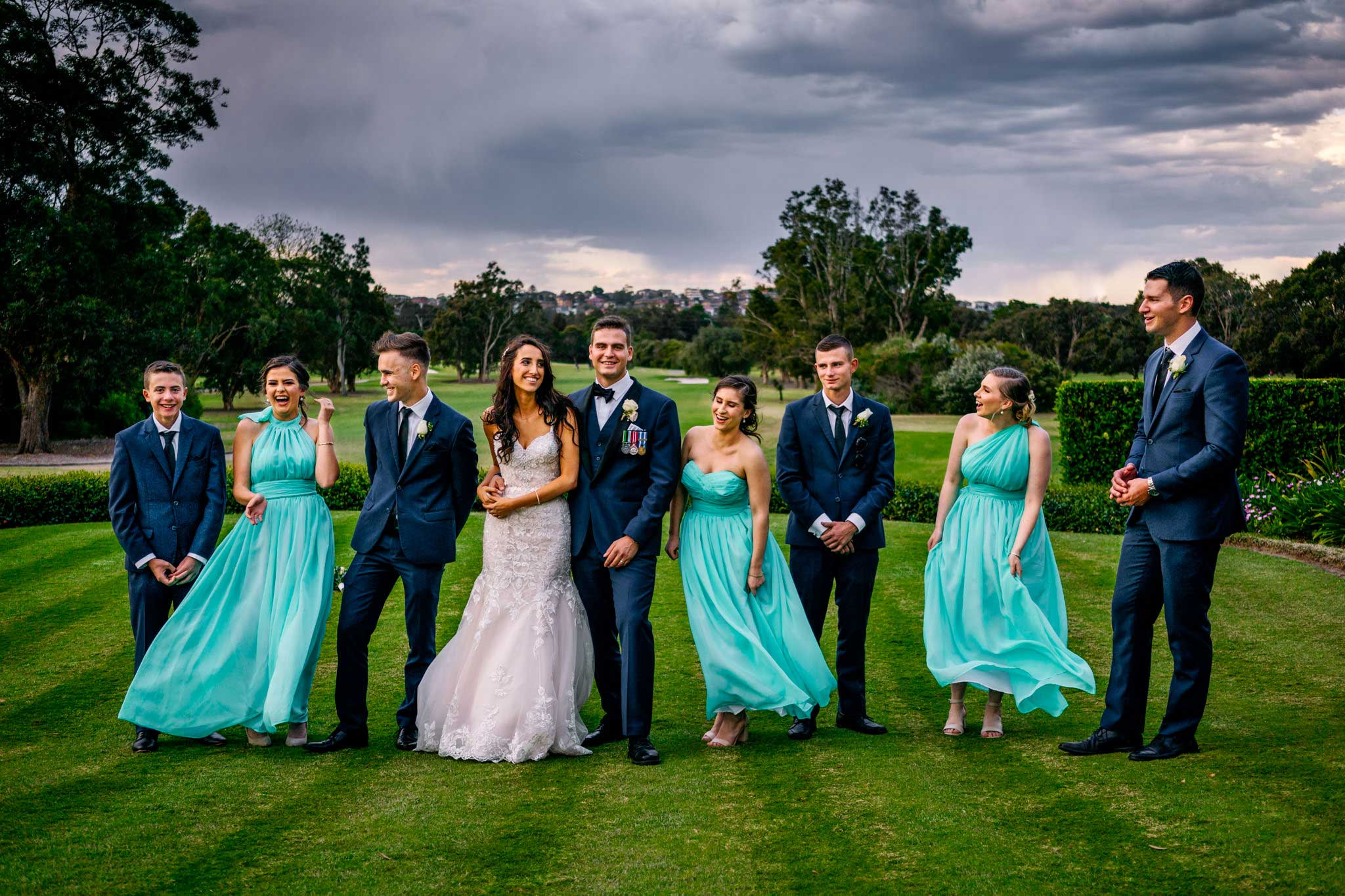 Bridal party laughing and playing on golf greens at Manly Golf Club
