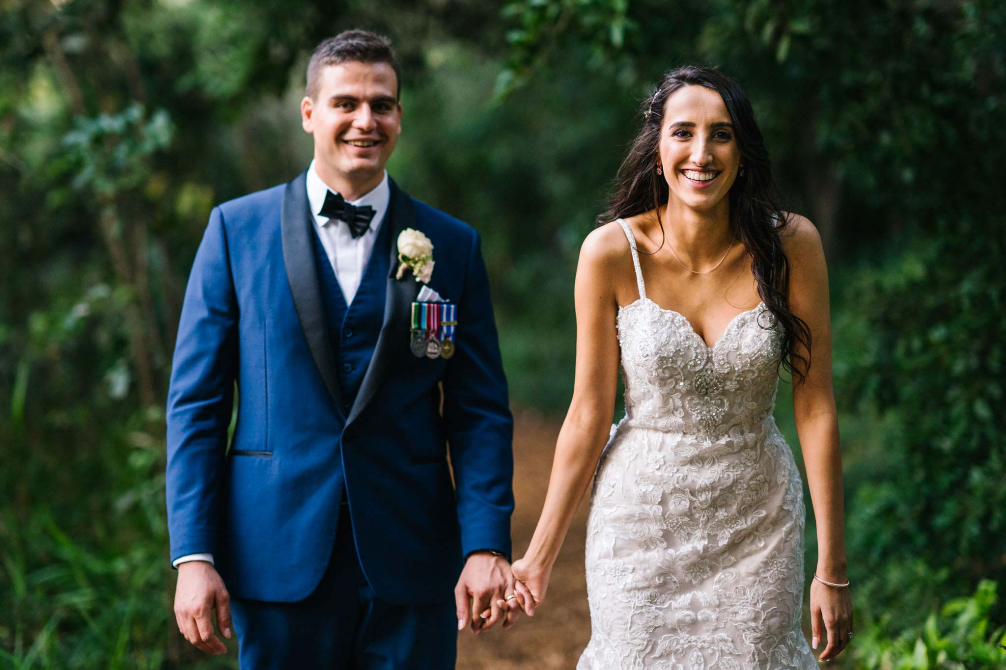 Groom and bride laughing as they walk through garden path at Manly Golf club