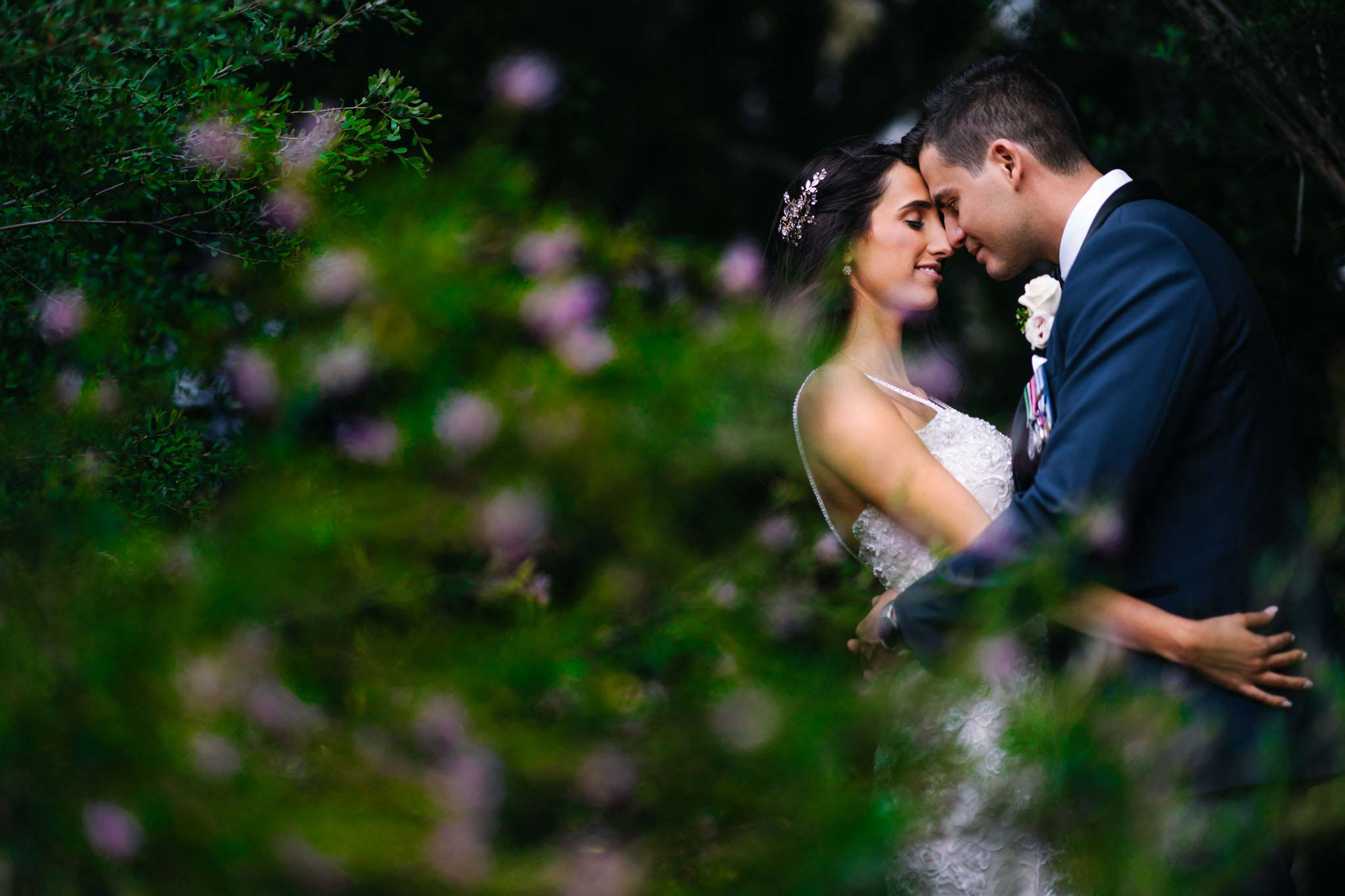 Newlywed couple embrace in the gardens at Manly Golf club in Sydney's Northern Beaches
