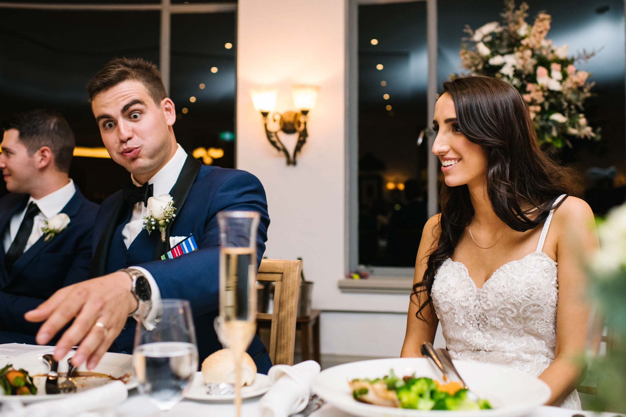 Groom makes a funny face as he reaches for his first drink at wedding reception