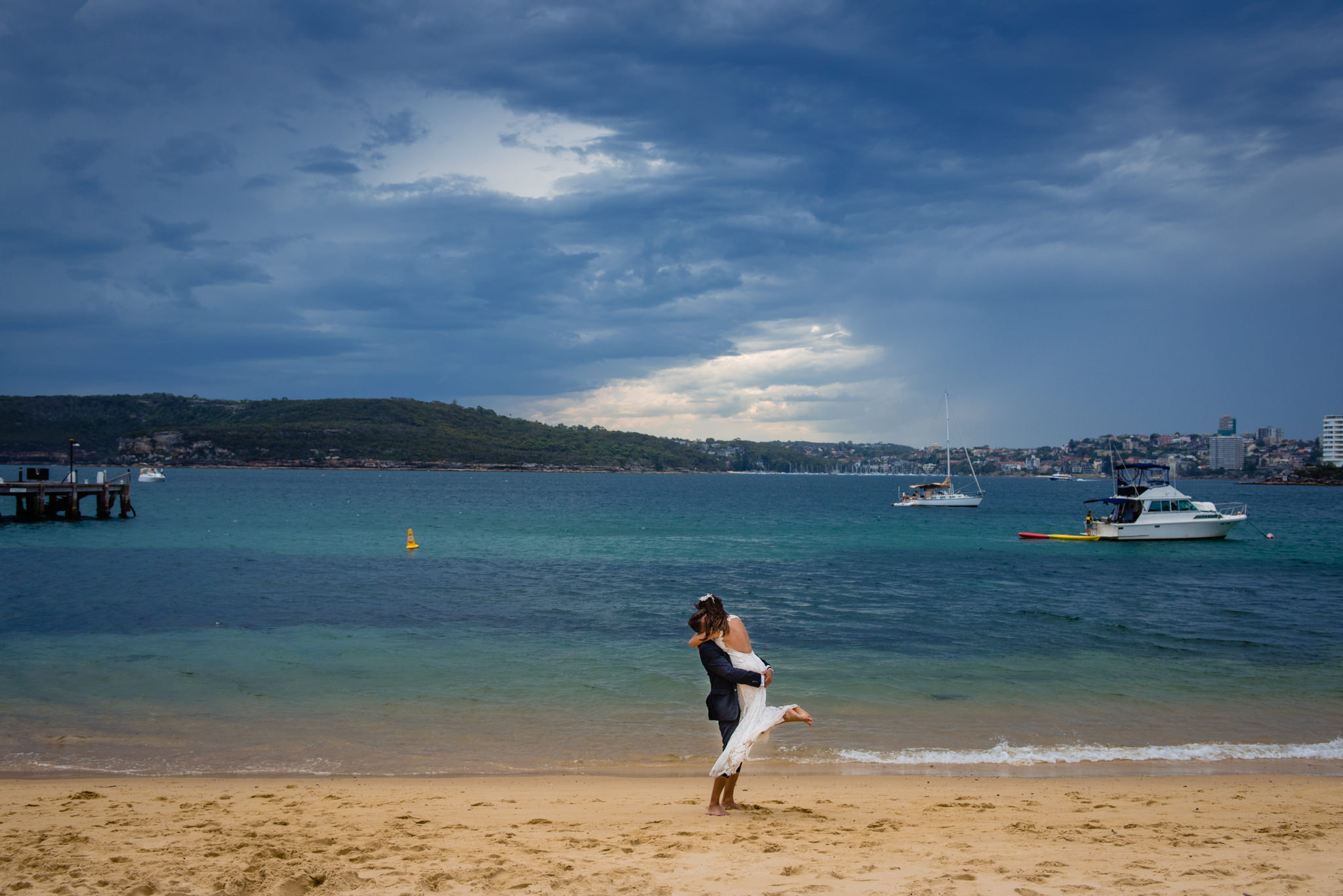 Newlywed couple embrace on beach at Q Station, Manly