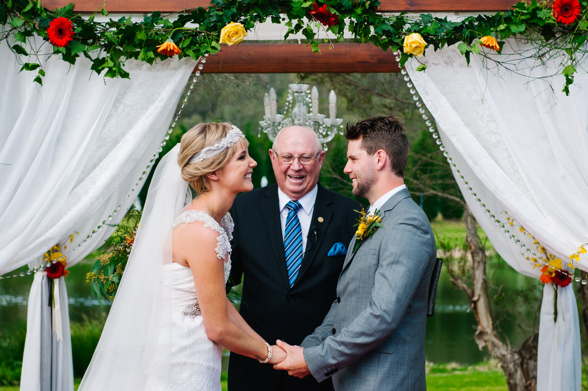 Bride and groom during ceremony under boho arbour at country wedding