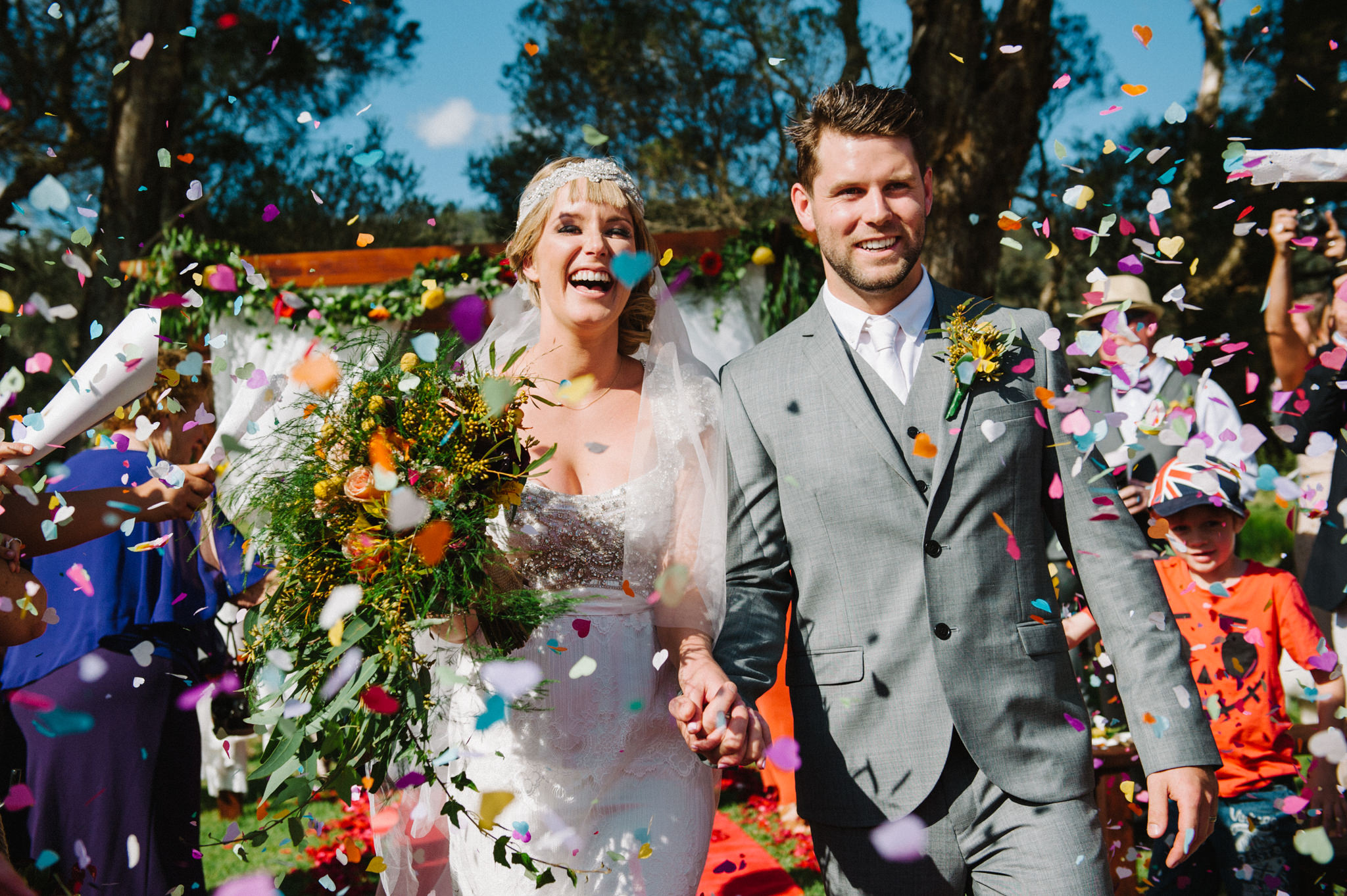 Happy newlyweds walking down aisle with rainbow confetti