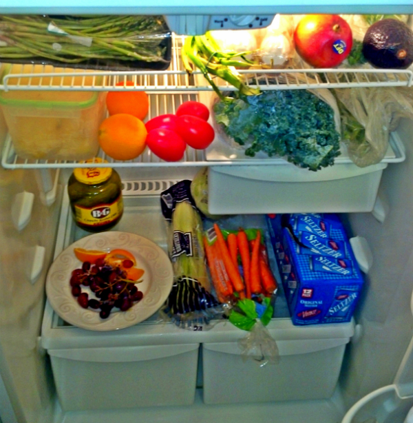 My Fridge From Left to Right : asparagus, scallions, eggs, mango, avocado, mint, line, chopped pineapple, tomato, orange, kale, mustard greens, pickles, grapes, celery, carrots, seltzer water, mustard, soy sauce, vegan butter