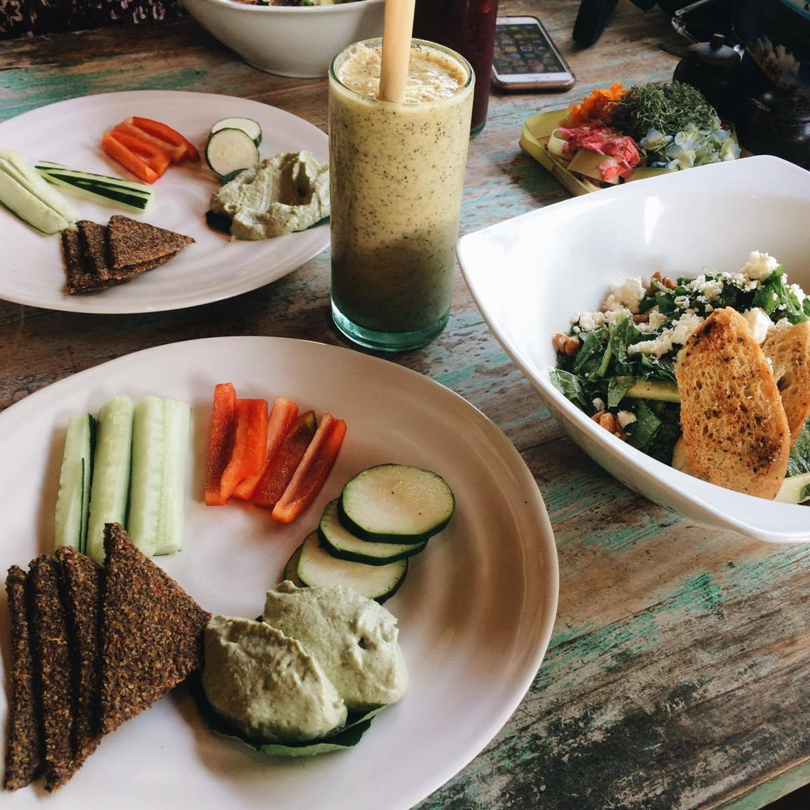 One Love- passionfruit, vanilla, mylk & honey and super high in plants sterols, blended smoothie    (Left) Smooth zucchini tahini hummus served with flax crisps and raw veggies    (Right) Grand Puri- wild greens, feta cheese, sliced apple & caramelised cashews ft. Clear's signature dressing