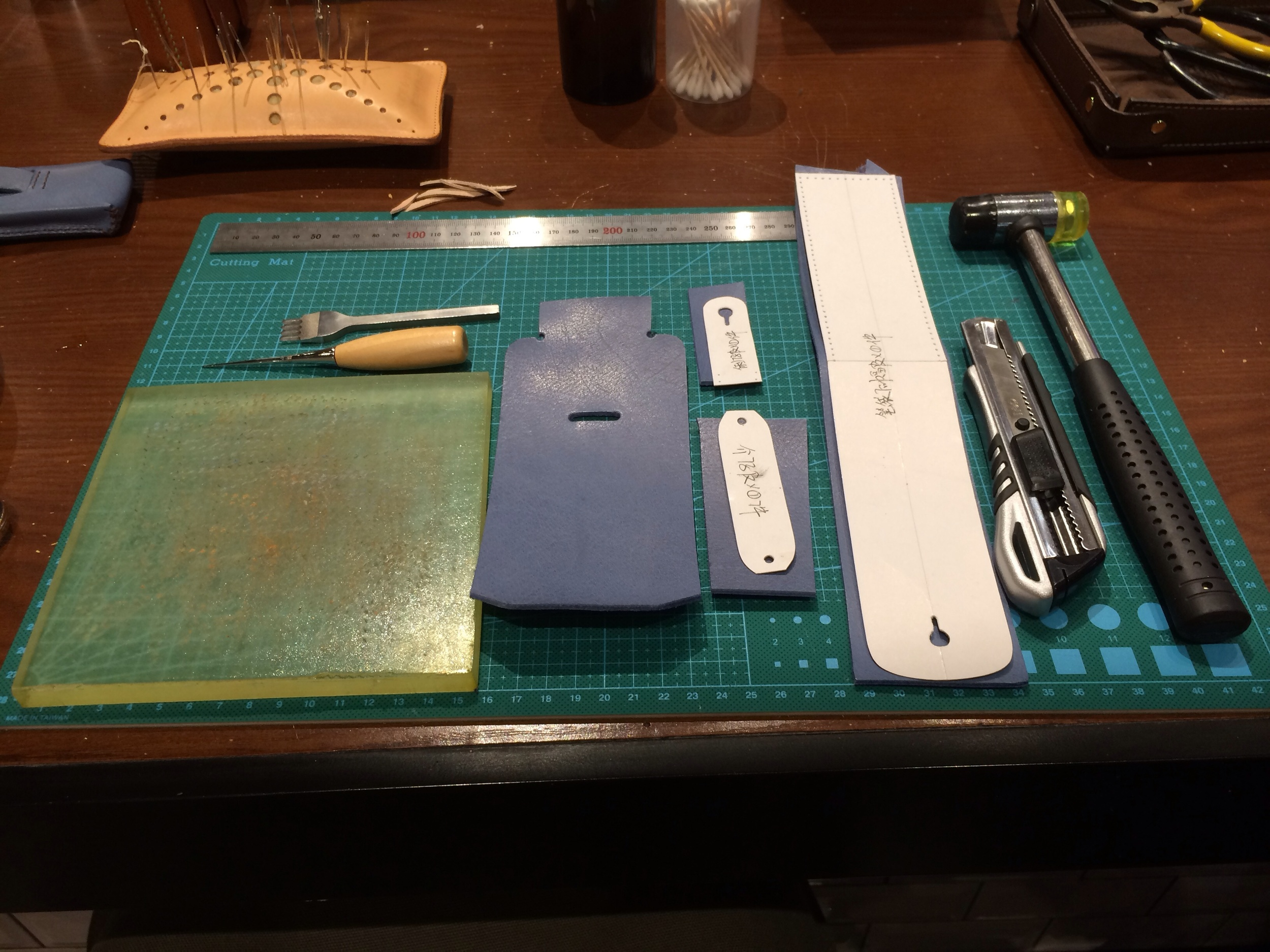 The tools required are laid out. Leather piece on far left is pre-cut and the other 3 pieces require cutting based on the paper patterns.
