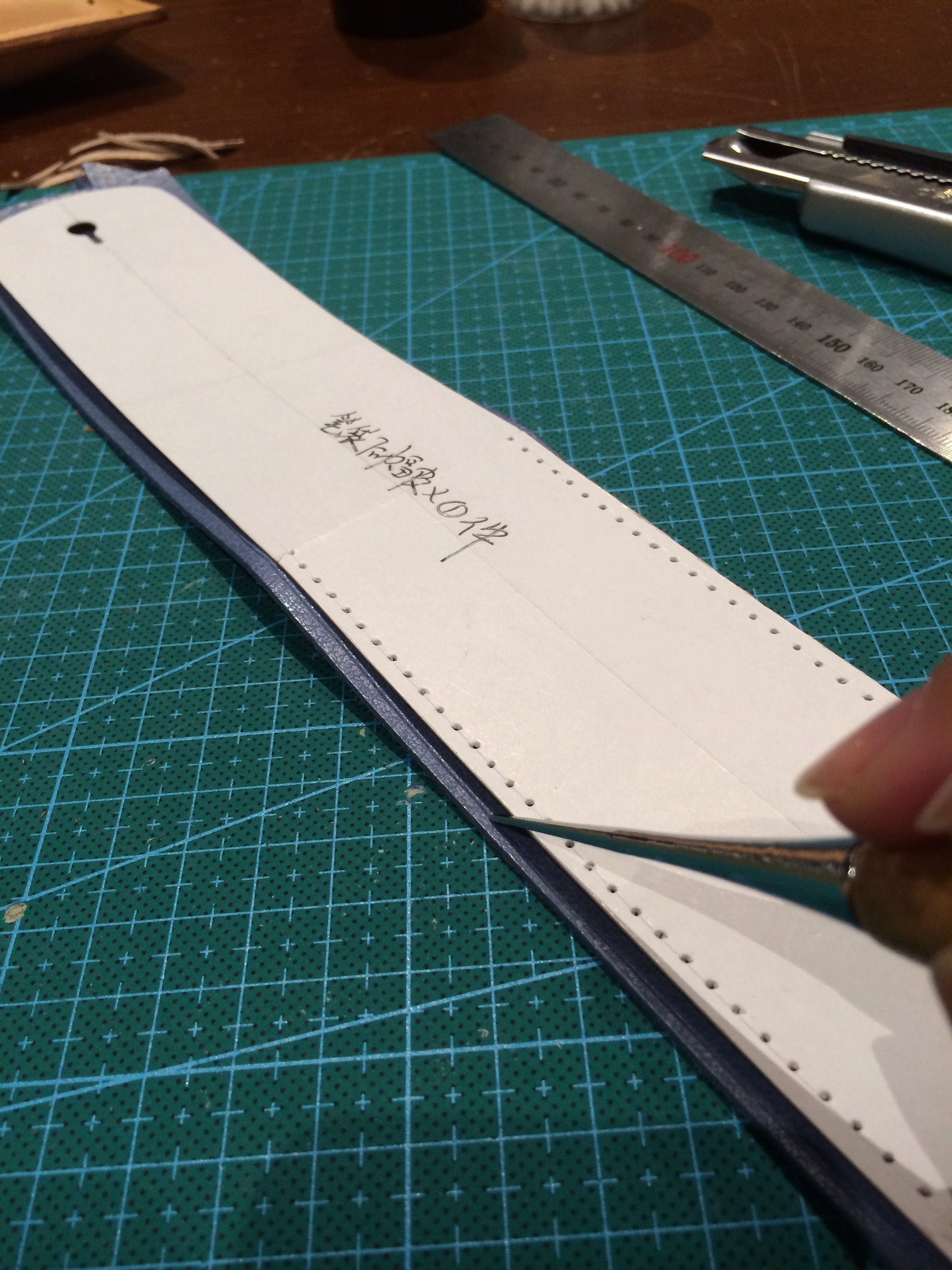 Tracing of the paper patterns using a metal tool with rounded tip. After scoring a line, we use a knife to cut the pattern out. Best to cut within the scored line, otherwise your leather will be bigger than the paper pattern.