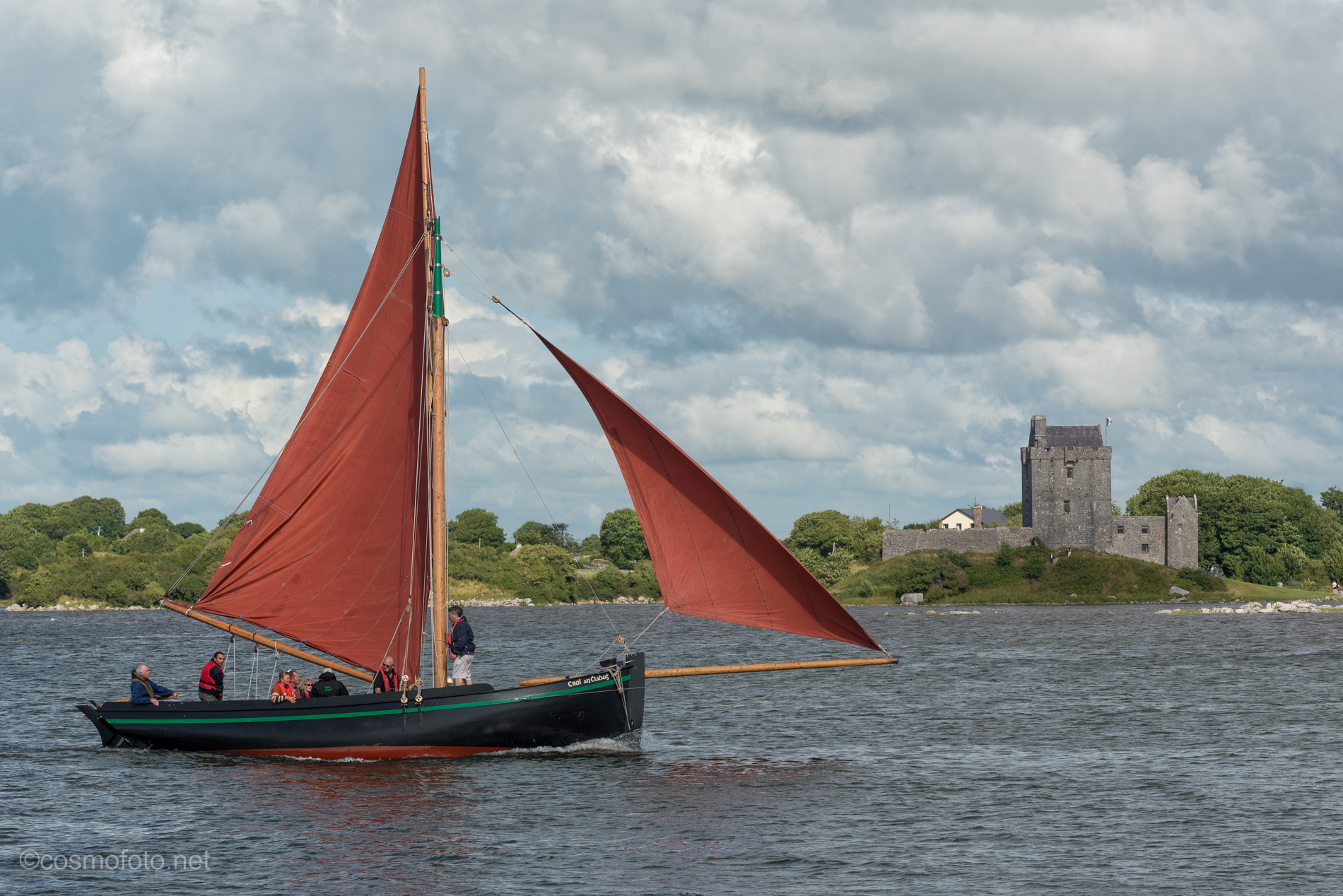 A hooker sails into Kinvara, Dunguaire castle in the background