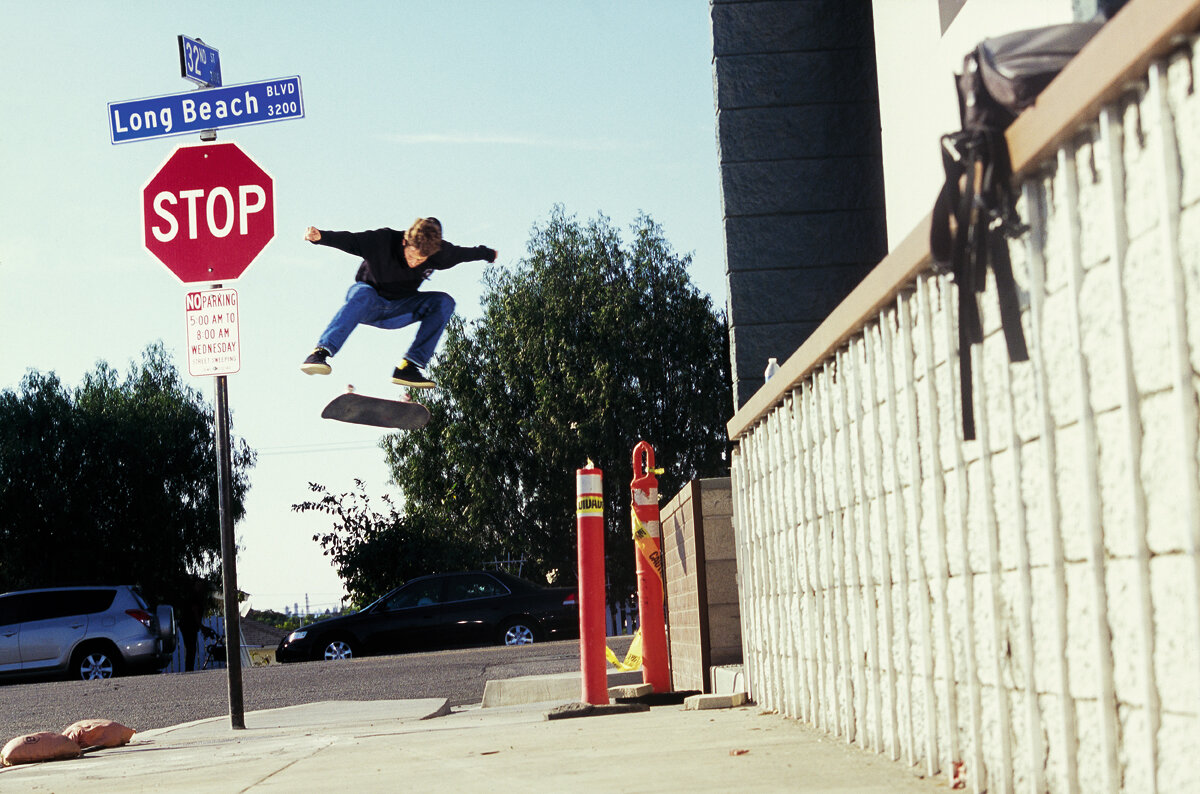 Julian Davidson and a backside kickflip over the sidewalk at a short-lived Long Beach, California spot.