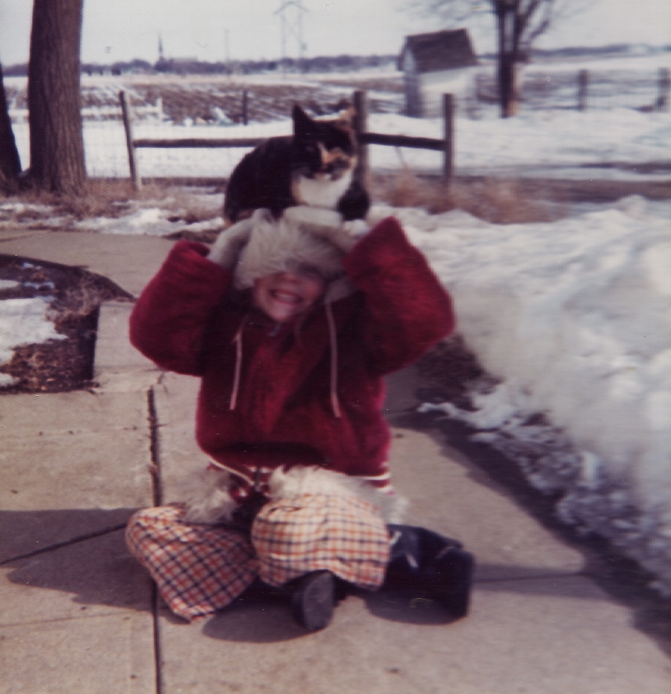 Me, circa 1973, with my cat, Flower. She loved to sit on my head! You can see our outhouse in the background. On a small hog farm outside of Humphrey, Nebraska.