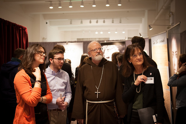 "Cardinal Seán P. O'Malley and other visitors walk through an exhibit entitled ""I am Exceptional: The Millennial Experience"" on Jan. 17 at the New York Encounter. Photo courtesy of Emily Marsolek"