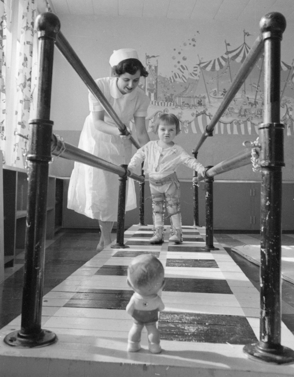 Sudbury Polio Clinic: Mrs. E. Marr, Physio-therapist, with Dorothy Gifford, 2 1/2 at the Walking Bars in the Polio Clinic , March 1953; Photographer: Chris Lund | Courtesy of National Gallery of Canada