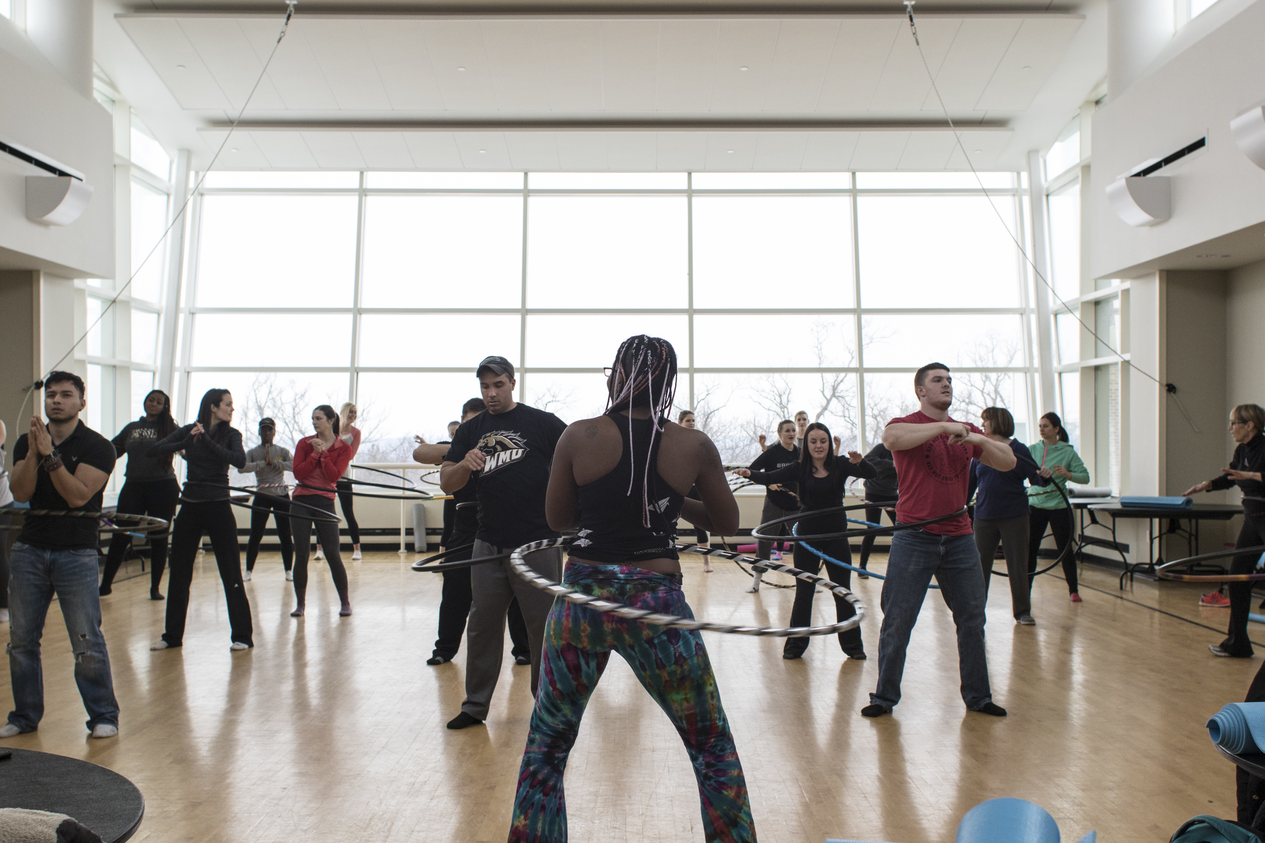 Shani led students in learning to waist hoop, offering tips to keep it circling, maintain balance, control, and correct stance and hip movement.