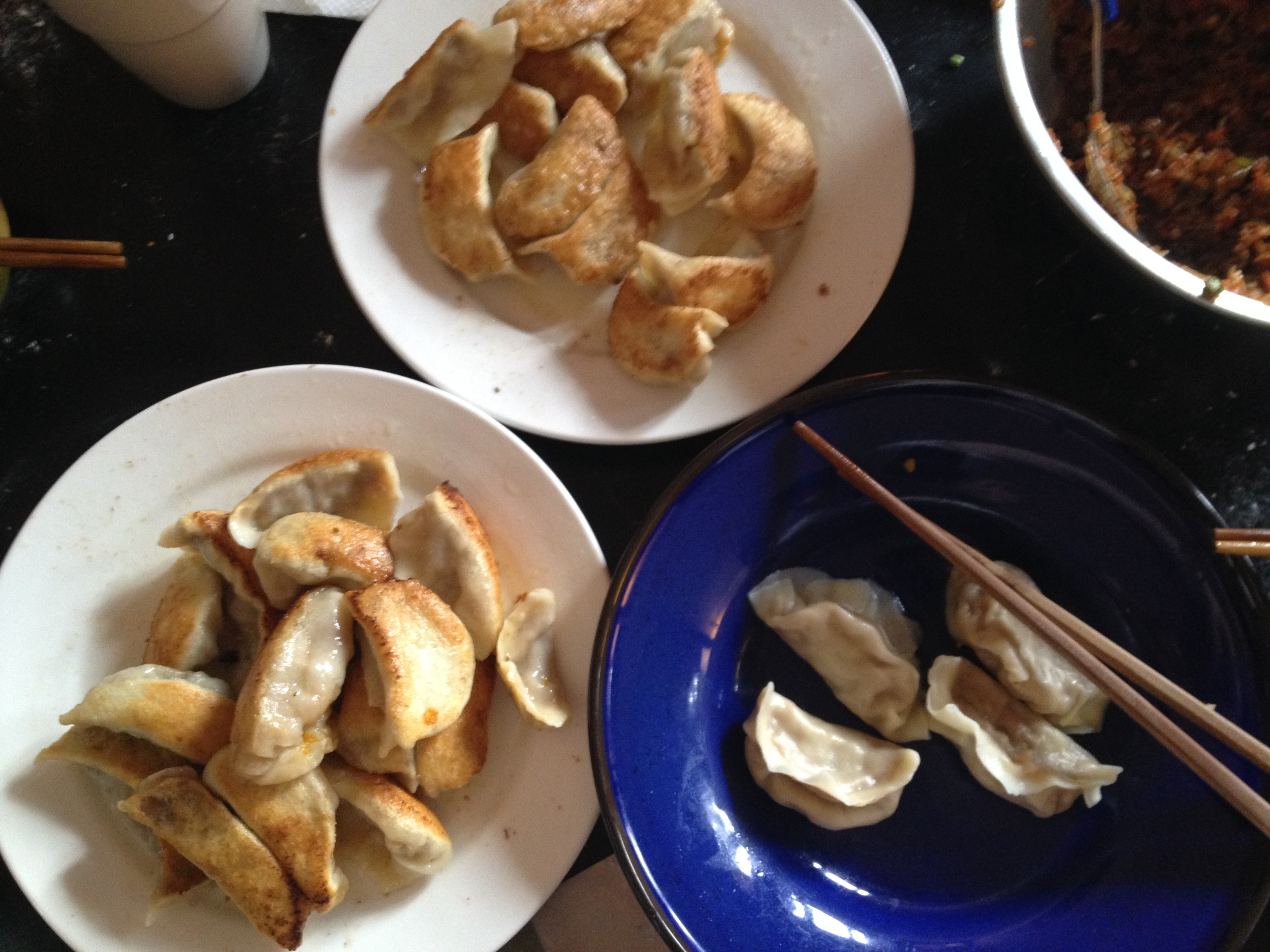 The finished dumplings. White plates are fried and steamed dumplings, the boiled ones are on the blue plate.