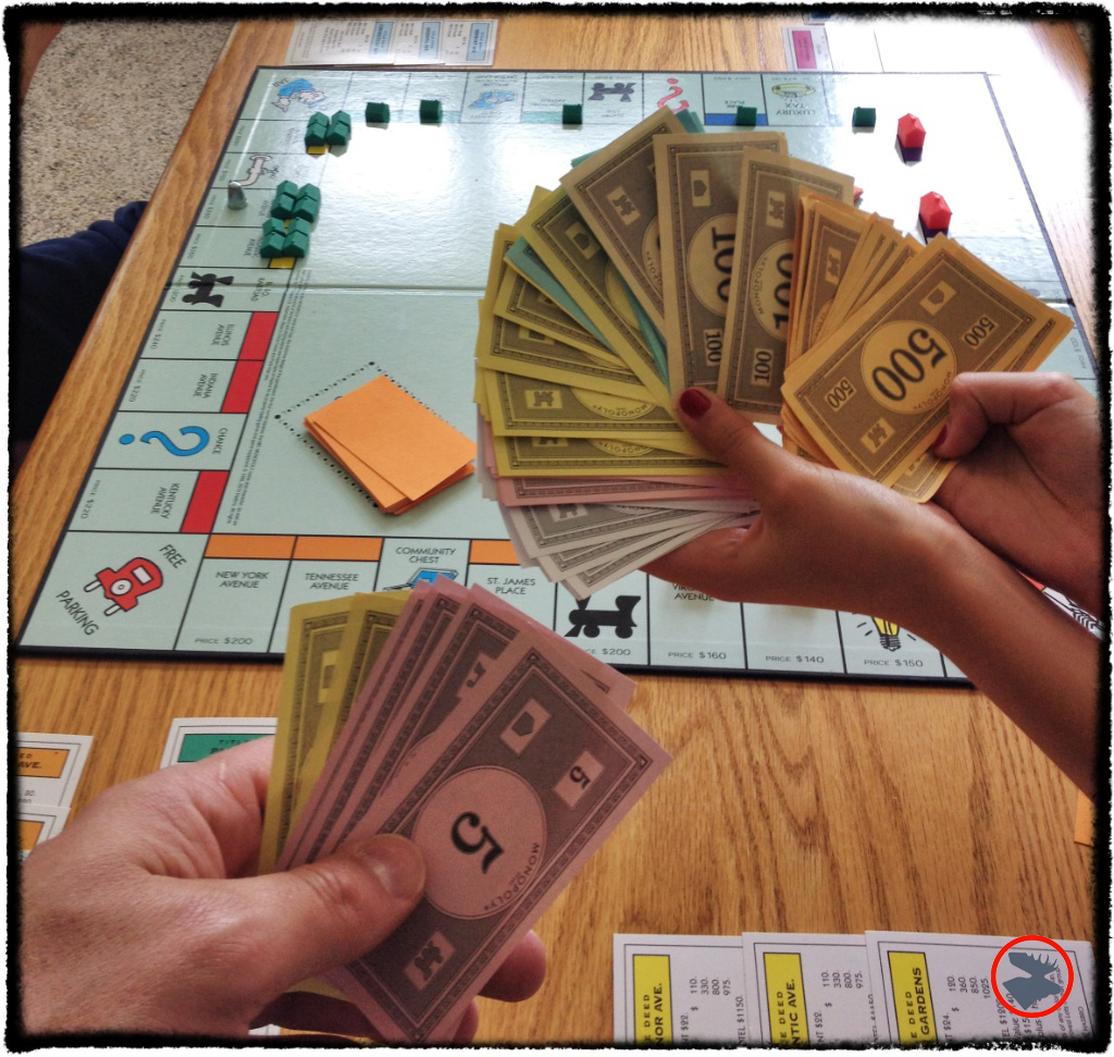 Parents get spanked in Monopoly. Hand on left holds a Bachelor's and Master's degree in Finance; the third graders' hand on right, holds all the money!