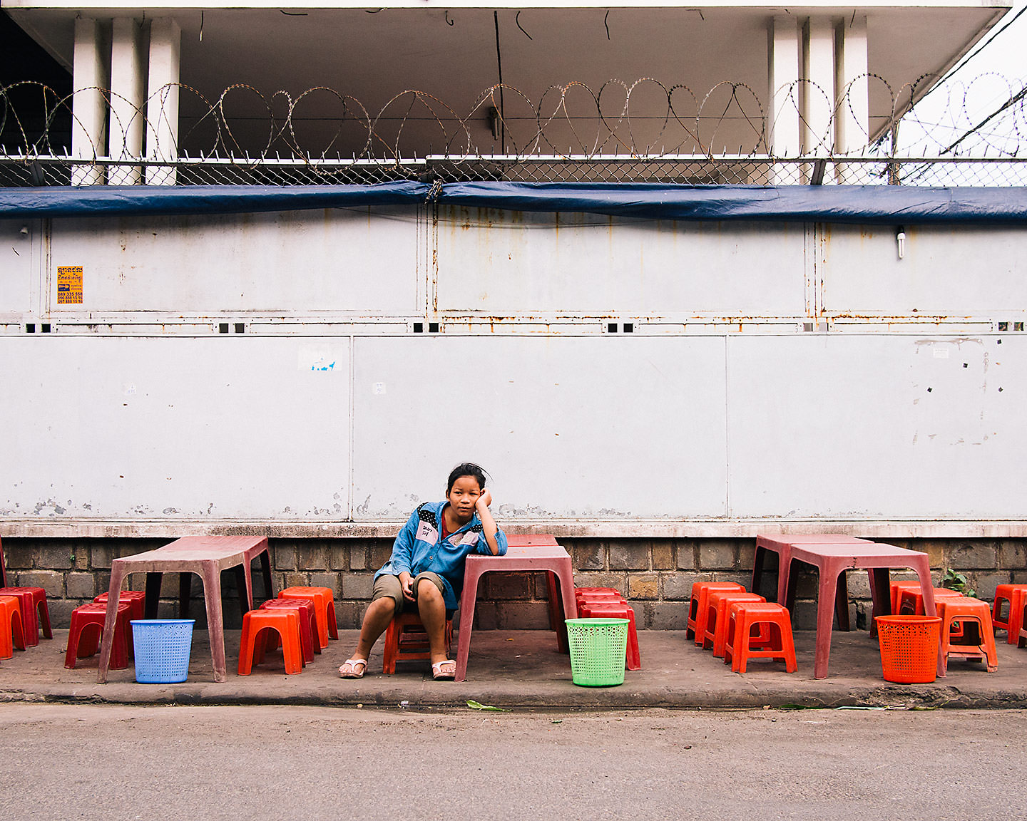 A young girl waits for the customers arrive at her family's roadside restaurant - Phnom Penh, Cambodia