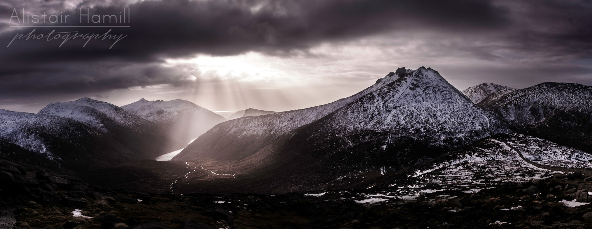 The summit of Bearnagh rises majestically over Ben Crom valley, bathed in the shafts of some winter light.