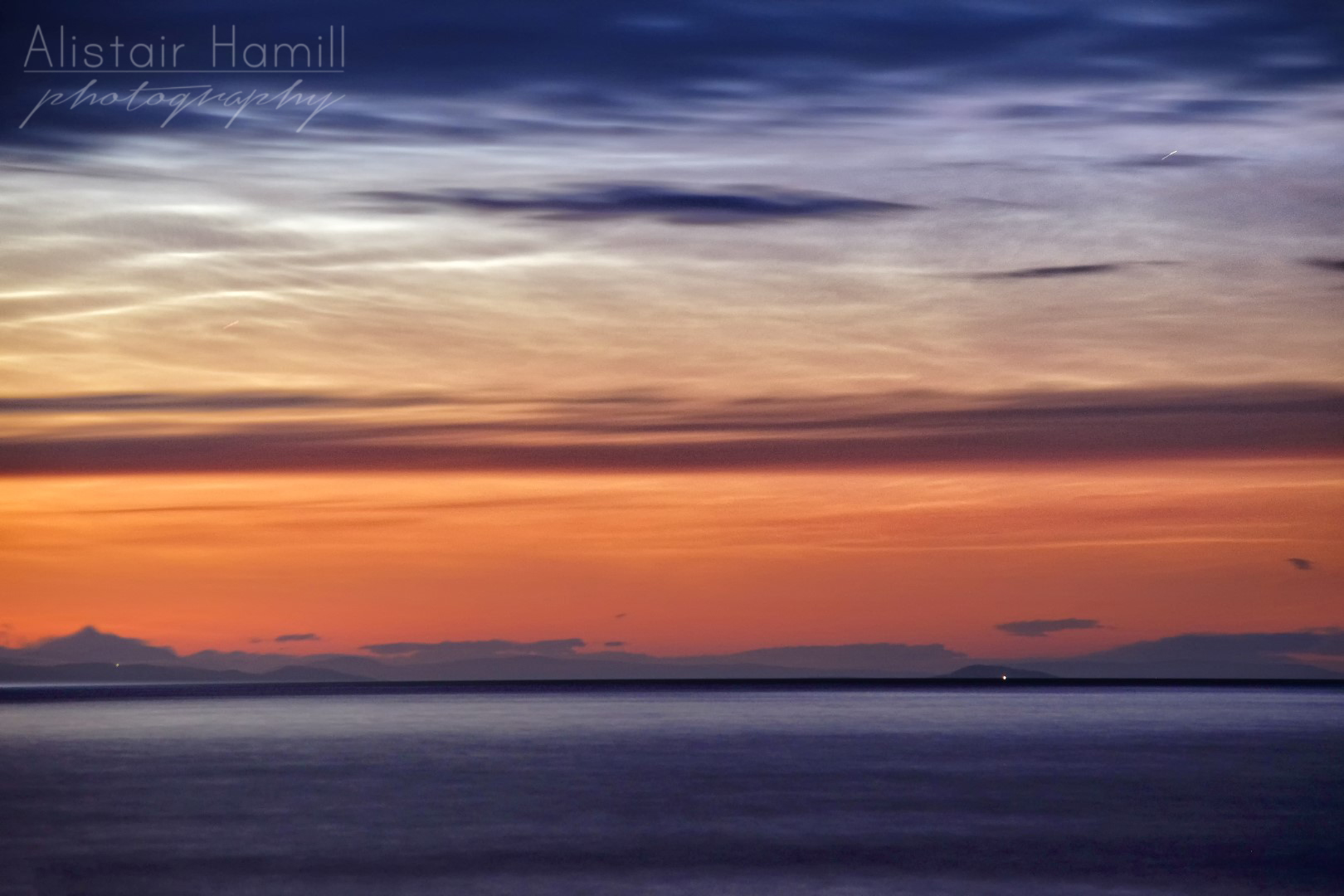 The lighthouse at Sanda Island shines all the way over to Garron Point, while the noctilucent clouds put on a wonderful display in the skies above.