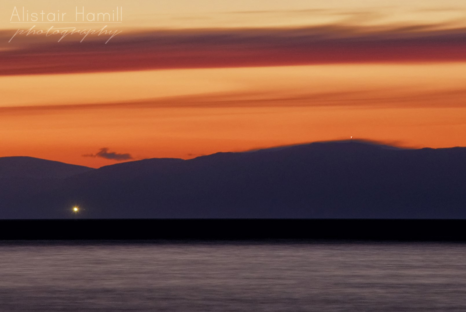 The lighthouse on Mull of Kintyre - along with a light on top of a hill top mast to the right just poking above some orographic cloud that is draped over the summit - have a close look to see if you can spot it!
