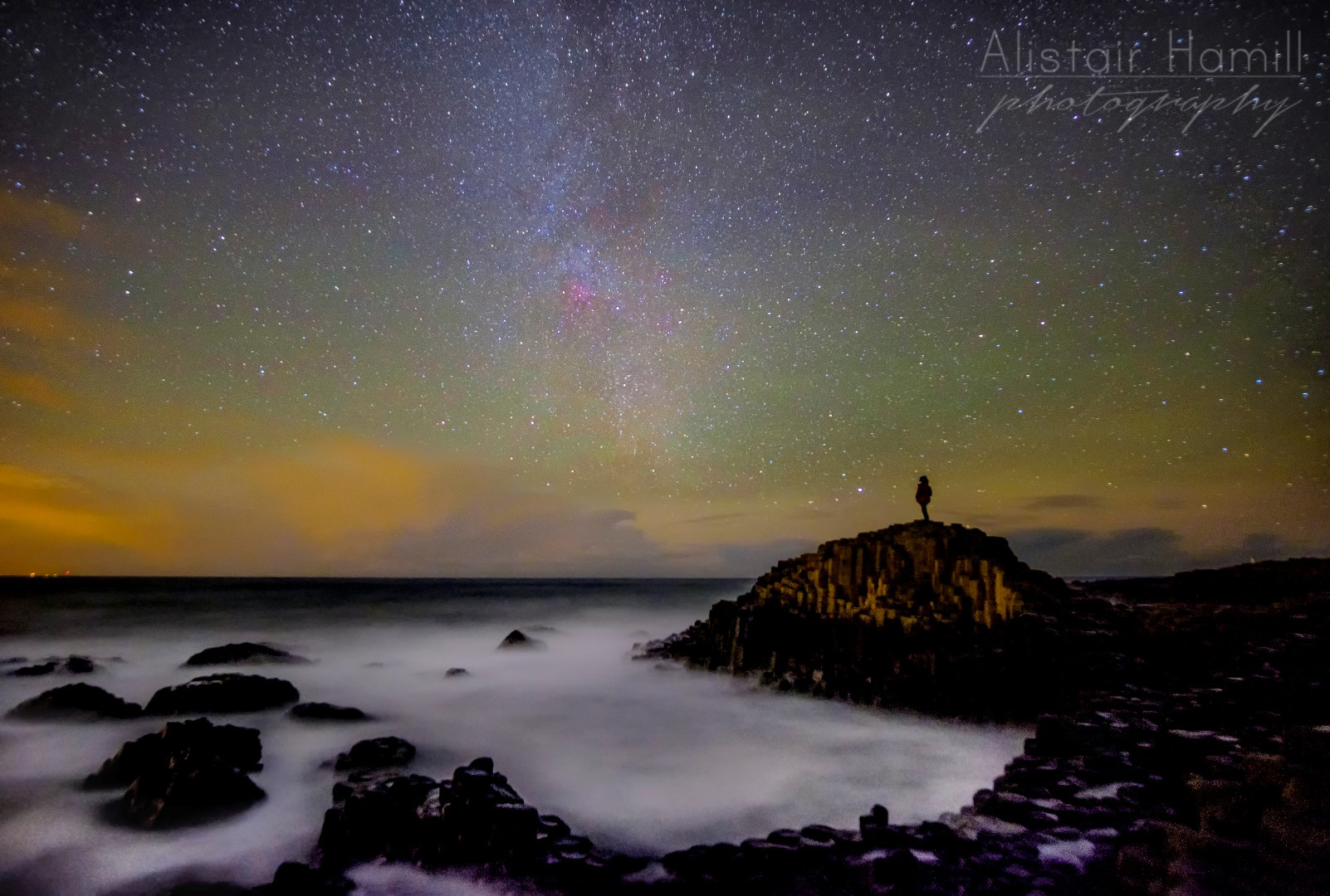 The pink glow of the North America Nebula hangs above the Causeway stones.