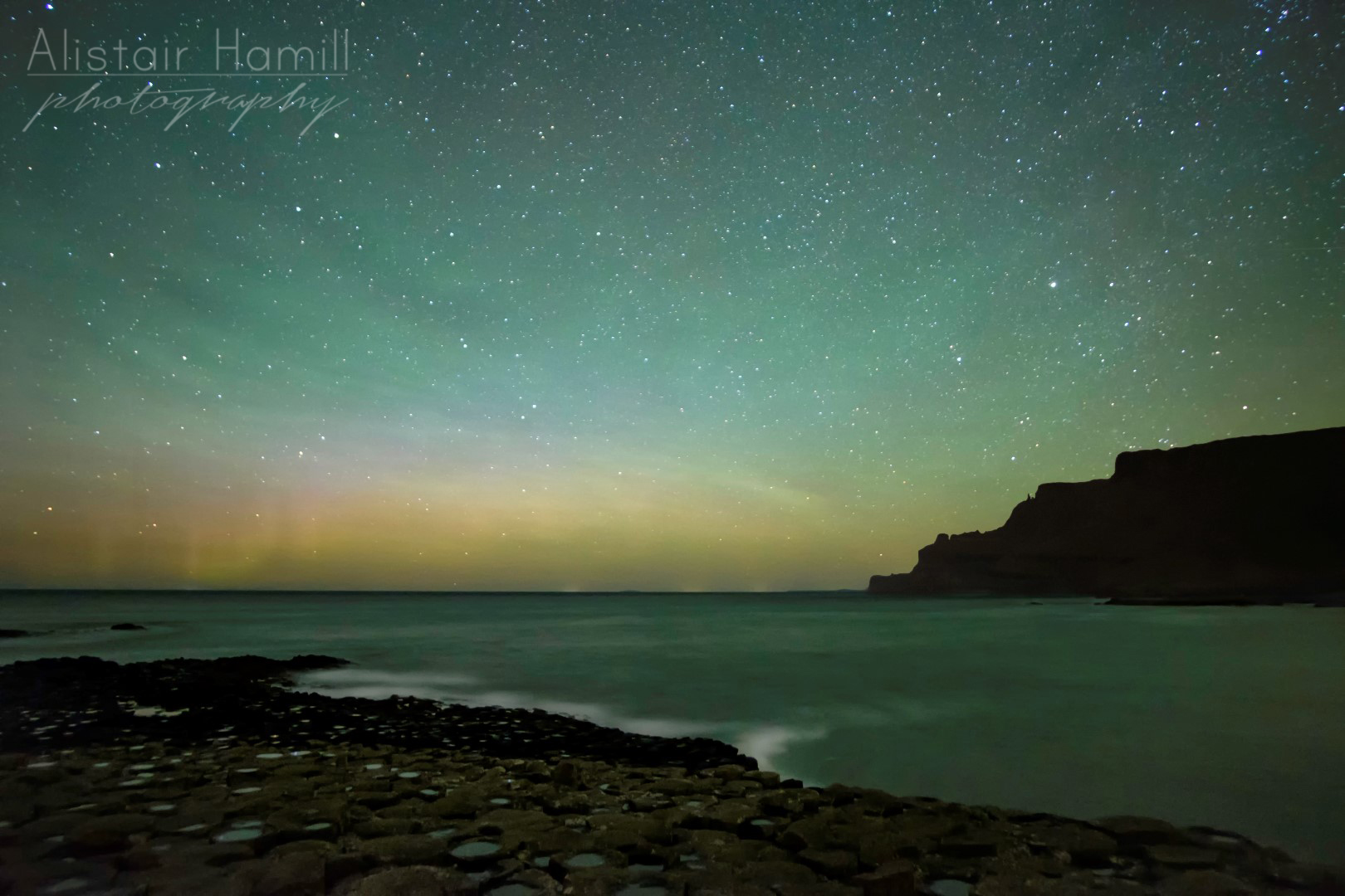 "The green hues of structure filled airglow reaches high into the sky, whilst the subtle aurora along the horizon throws up some faint pillars, as if to say, ""Don't foget about me!"""