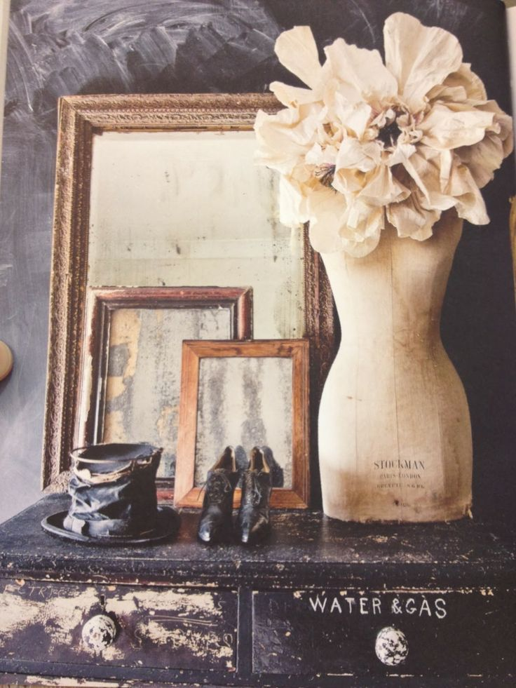 I love this one...your eyes starts with the top hat and shoes then travels up to the mirrors which are in three sizes, the shortest mirror is in line with the waist of the mannequin which draws your eye to the right and up to the flower at the top.