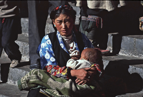 Tibetan woman breast feeding her child on Barkhor Street