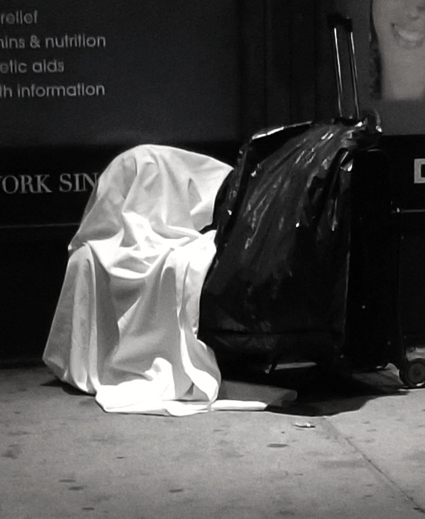 A holy ghost in Gehenna... a homeless person in a white sheet with black bag. Murray Hill, Manhattan, New York.