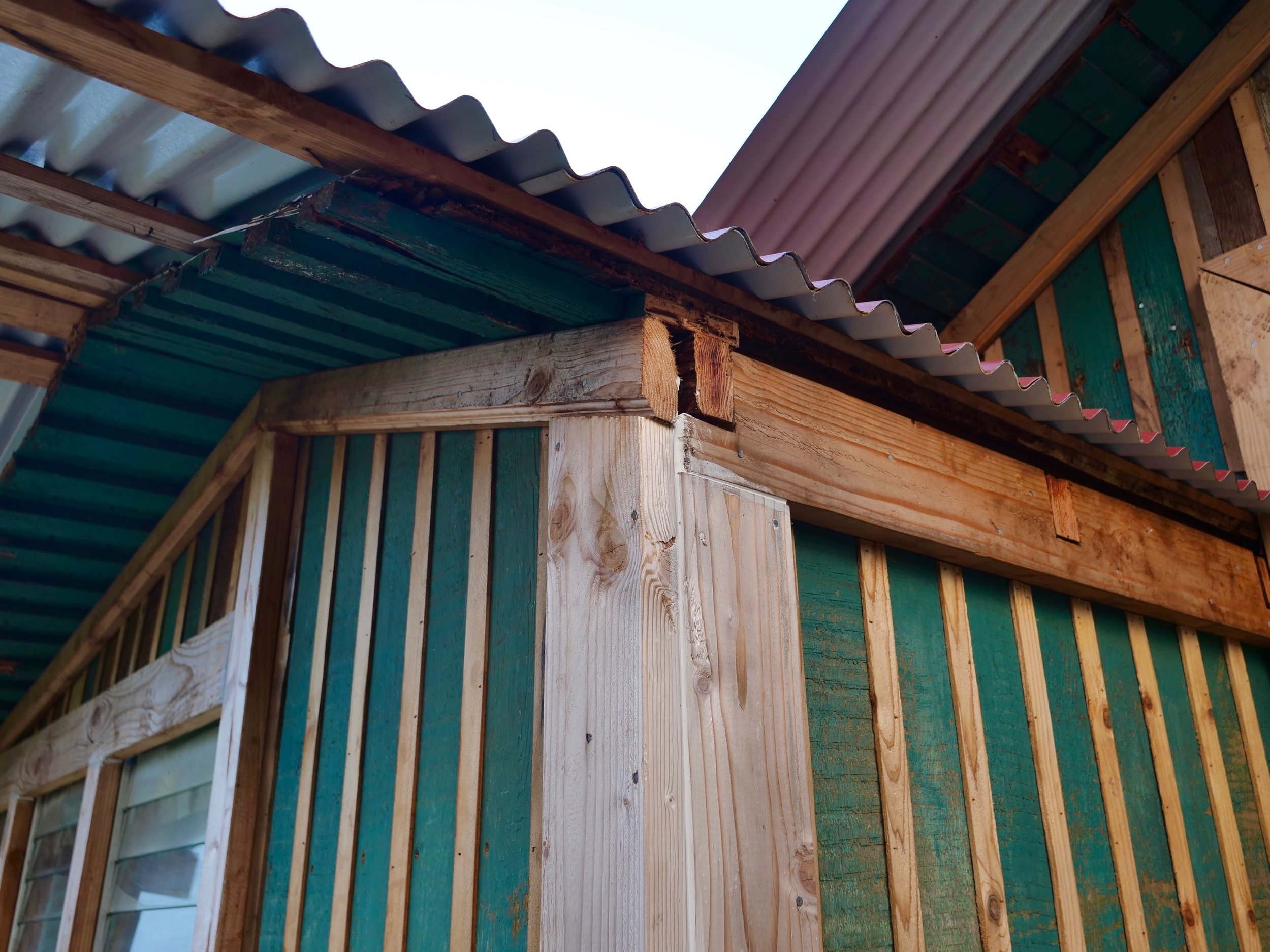 Single wall construction: tongue and groove walls with cedar strips covering the seams, and a tin roof.