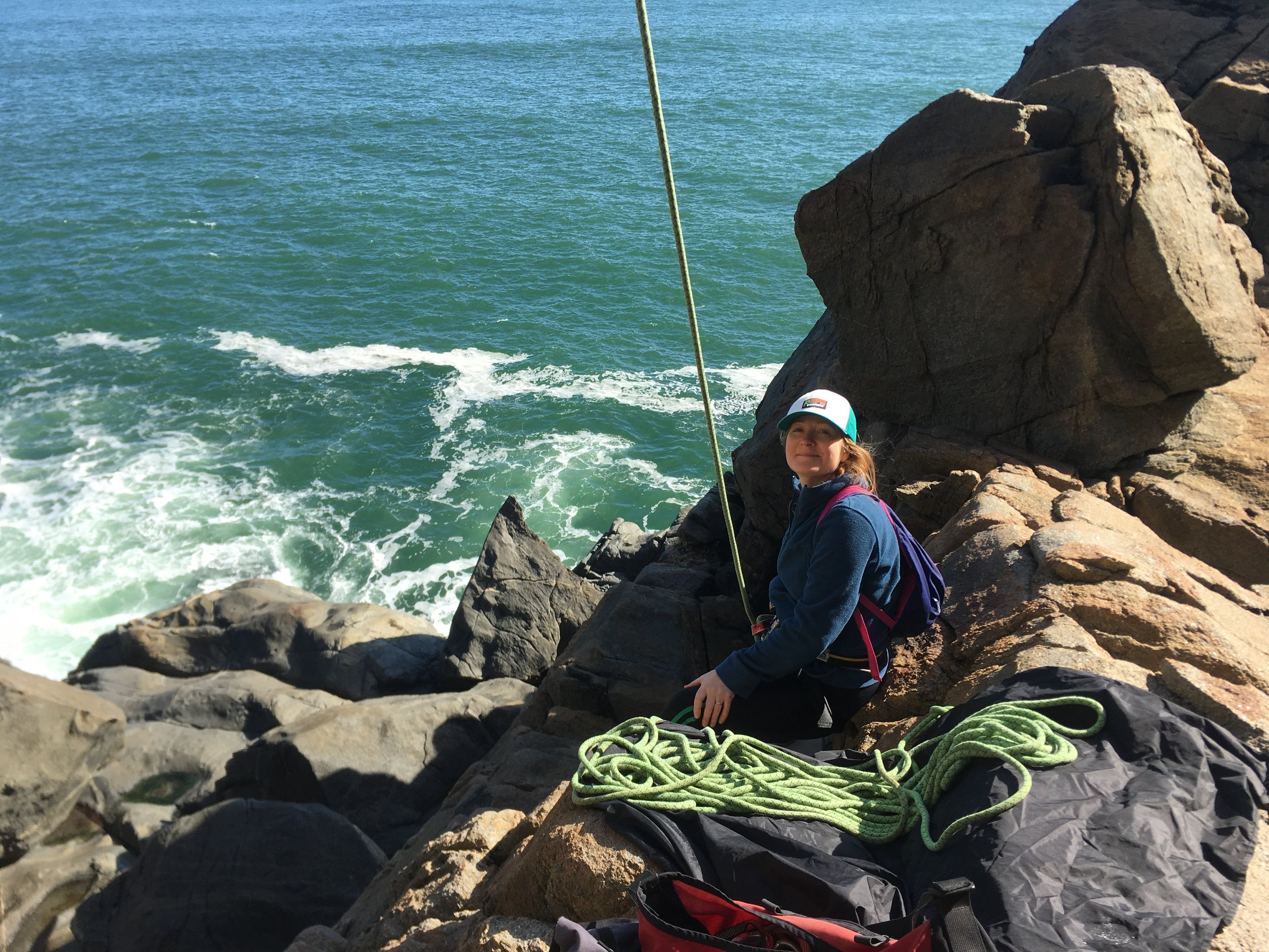 Emily belaying cliffside