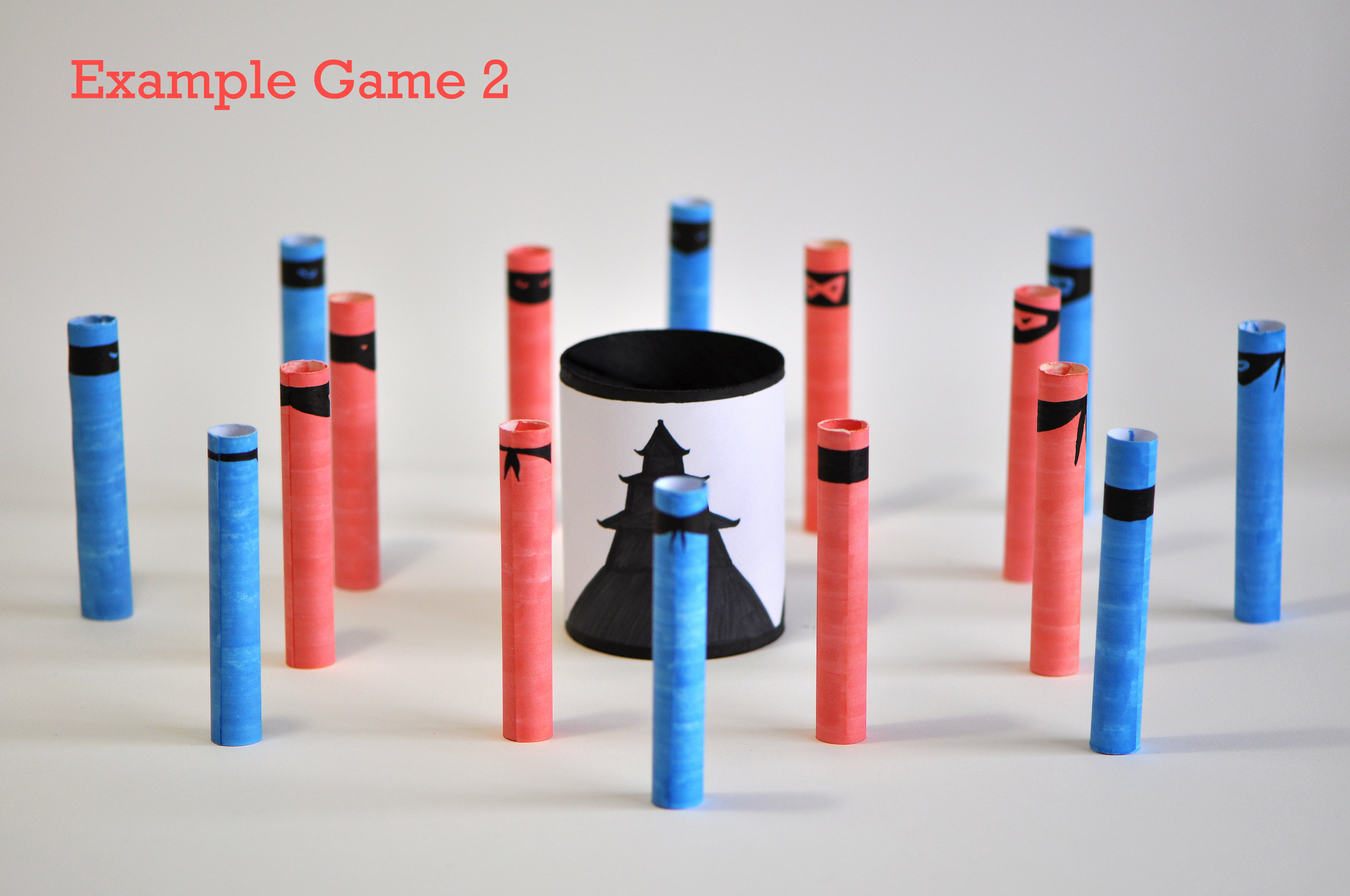 Two or more players (two players in this setup) all try to hit the blue ninjas and avoid the red ones. If a red ninja is knocked down, the kill doesn't count and all red and blue ninjas hit in this turn must be put back up. At the end the person having killed the most blue ninjas wins.