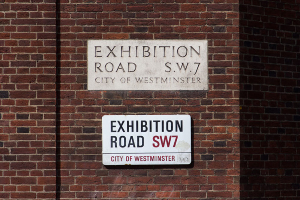"""""""A fine pair of signs here on the 1930s extension to the Grade II* listed  Royal Geographical Society. The incised stone plaque presumably dates  from the construction of the extension – the lettering style is very  elegant, though the spacing is slightly uneven. Below it sits a  (slightly superfluous) example of Design Research Unit's enamel  nameplates for the City of Westminster, designed in 1968 by Misha Black  and Christopher Timings. These feature a bespoke alphabet based on  Univers, designed by the practice specifically for use on the signs.  Unfortunately, recent signs produced for Westminster have started to  appear using Helvetica Condensed instead."""""""