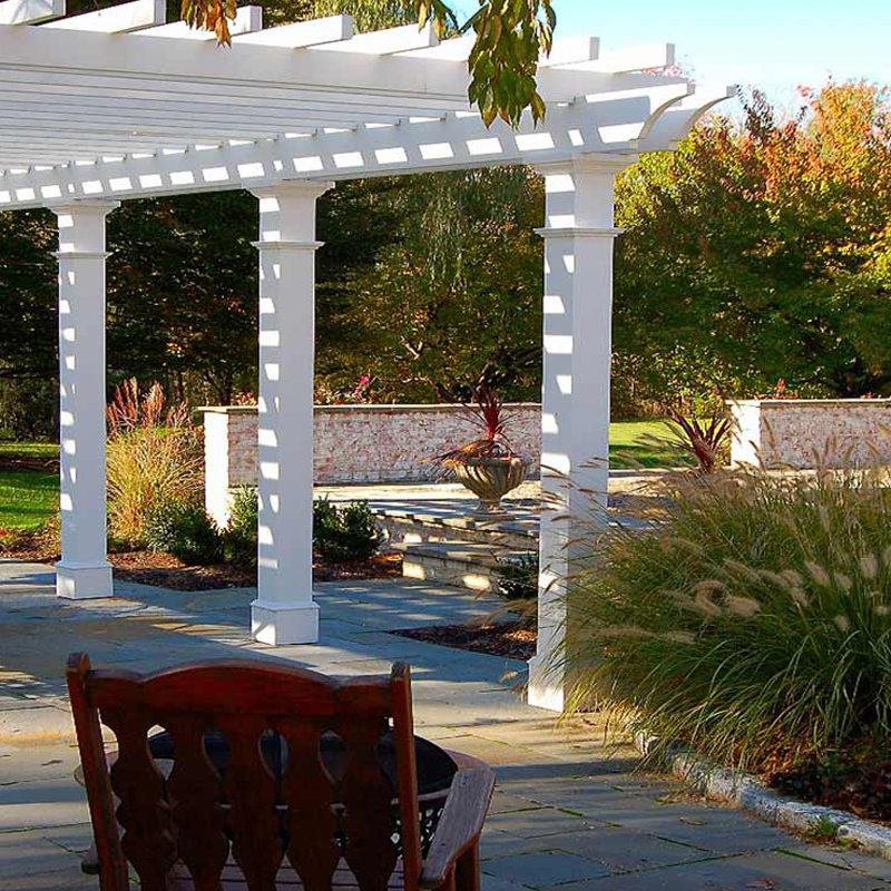 Traditional Landscape in Lancaster Pa. with a central water feature a pergola and an outdoor kitchen.